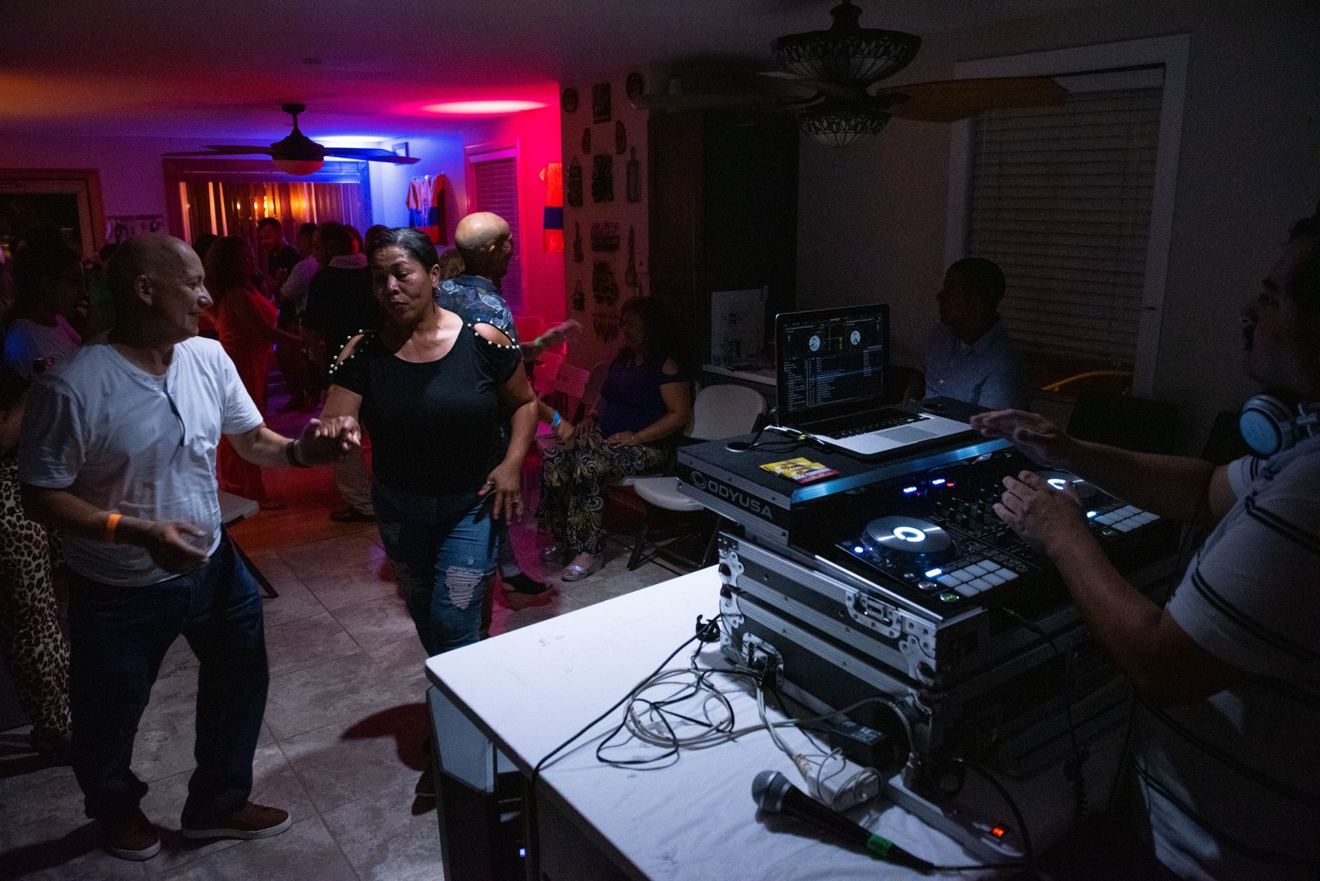 Guests dance from the kitchen to the living room at a viejoteca in Oxford Circle on Sunday, September 15, 2019.