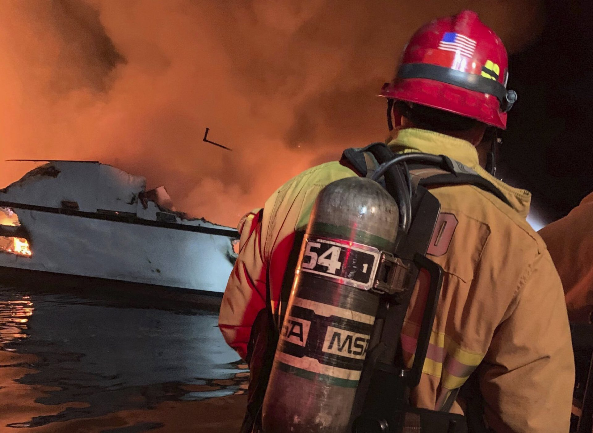"""In this photo provided by the Ventura County Fire Department, VCFD firefighters respond to a boat fire off the coast of southern California, Monday, Sept. 2, 2019. The U.S. Coast Guard said it has launched several boats to help over two dozen people """"in distress"""" off the coast of southern California."""