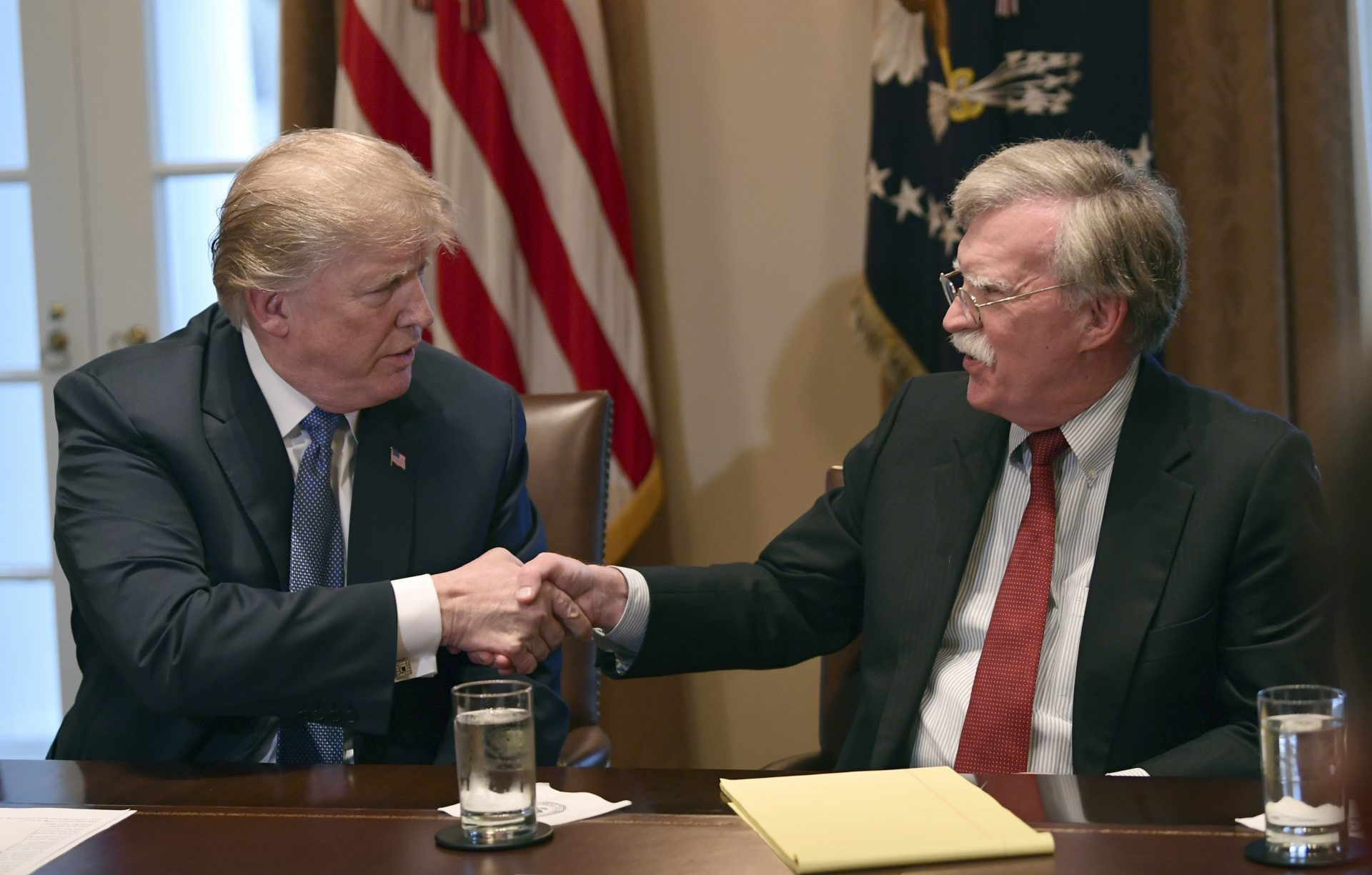 In this April 9, 2018 file photo, President Donald Trump, left, shakes hands with national security adviser John Bolton in the Cabinet Room of the White House in Washington at the start of a meeting with military leaders. Trump has fired national security adviser John Bolton.