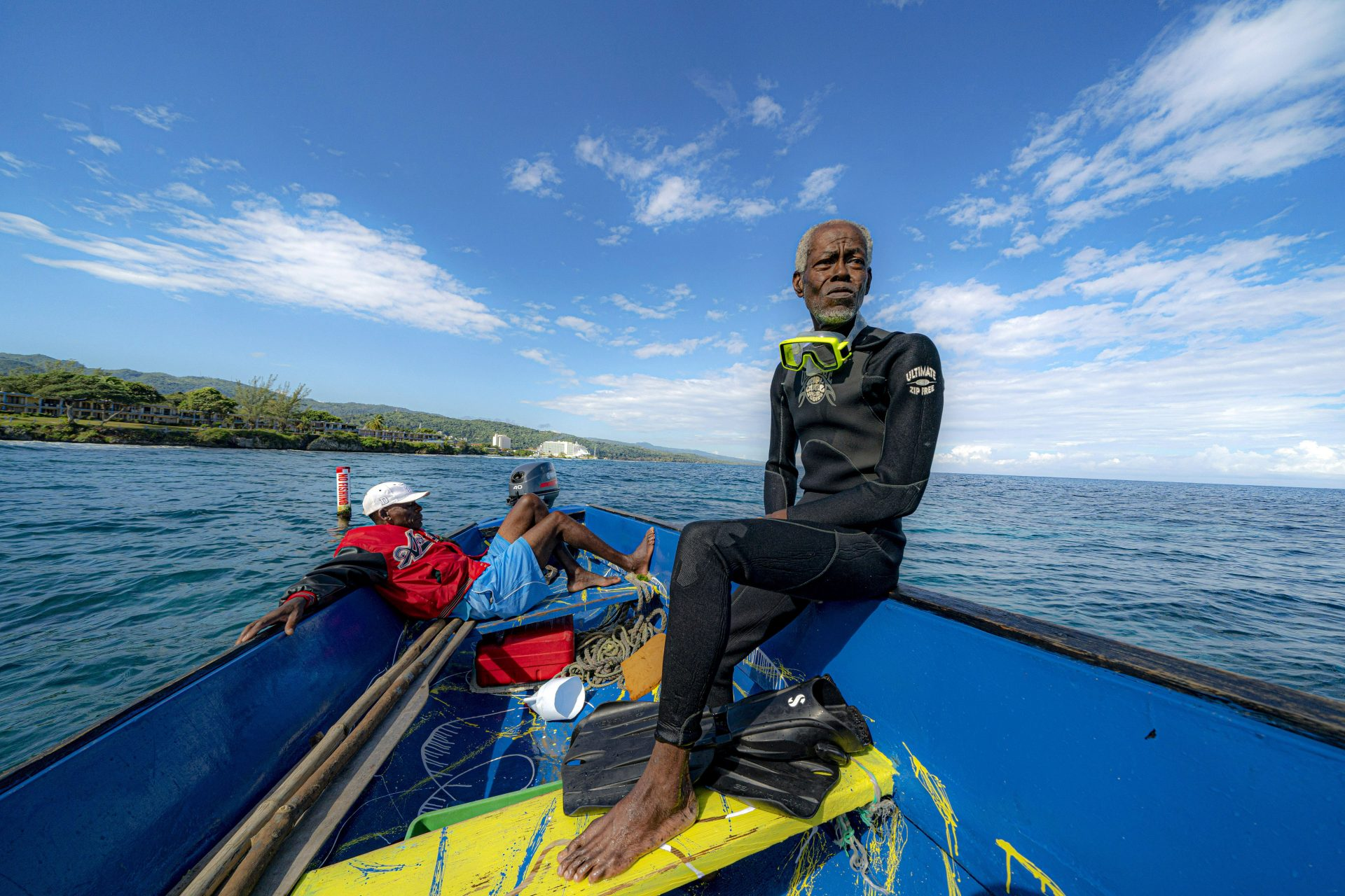Everton Simpson, right, sits on a boat in-between dives on the White River Fish Sanctuary with Mark Lobban, left, Monday, Feb. 11, 2019, in Ocho Rios, Jamaica. More than a dozen grassroots-run fish sanctuaries and coral nurseries have sprung up on the island in the past decade.