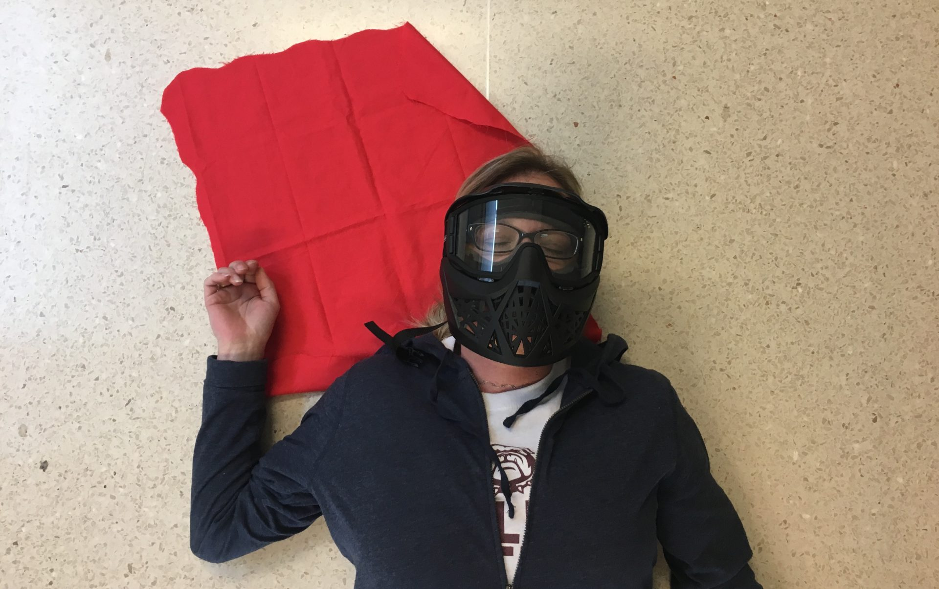 Angie lies on the ground, playing dead during a FASTER school shooting simulation.