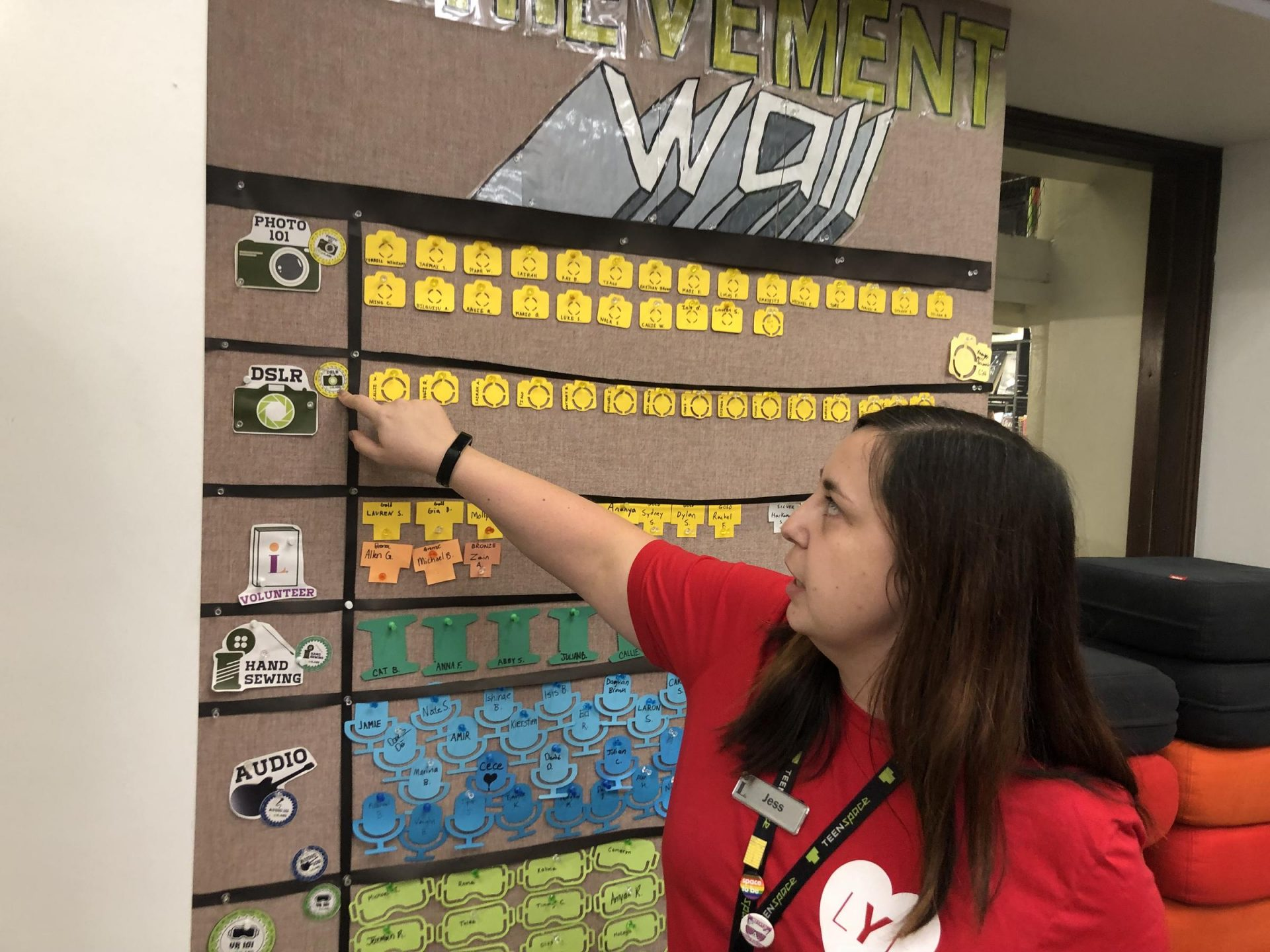 Carnegie Library of Pittsburgh teen librarian Jess Smith points to the achievement wall, where students can accumulate badges after learning a new task, like sewing or DSLR camera operating. The teen space in the main branch was once called the Colonel James Anderson Reading Room, after the man who opened his private library to working boys, including Andrew Carnegie.