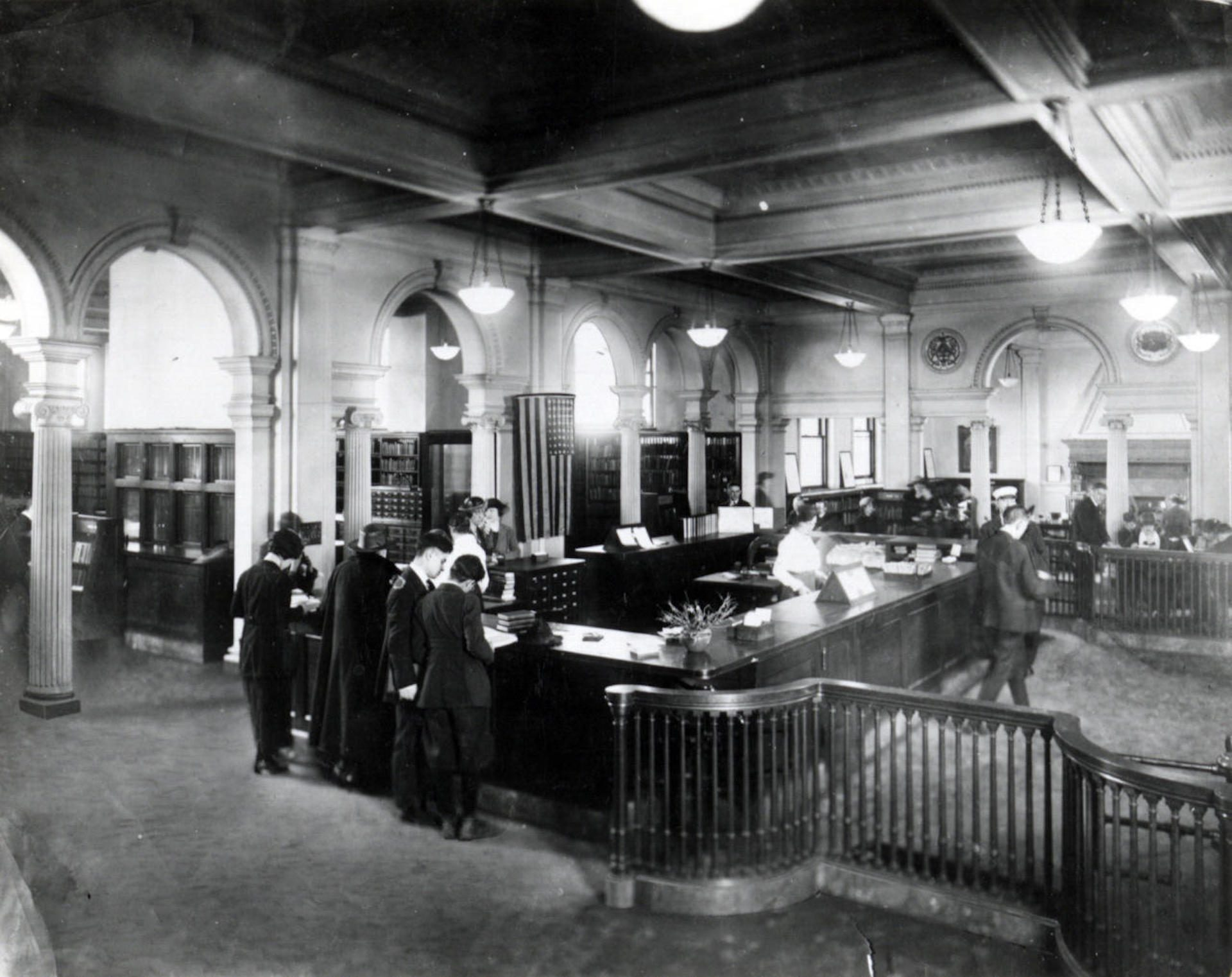 A circulation desk at the Carnegie Library of Pittsburgh around the late 19th, early 20th century. Prior to the library's open stack approach, only librarians could find and check out books for visitors.