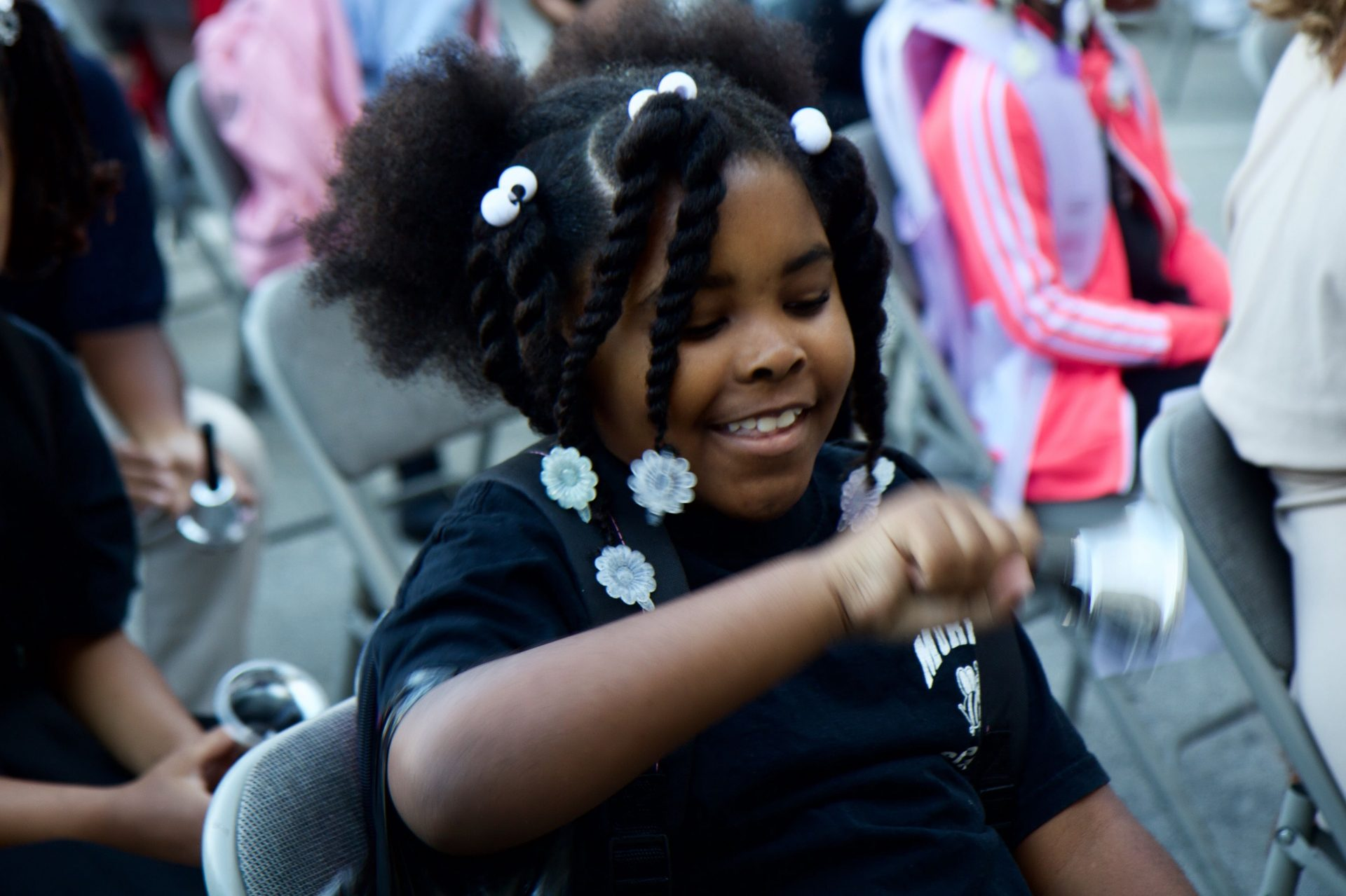 2nd grader Navayah Reynolds rings in the new school year at the 2019 start of school bell ringing ceremony in Philadelphia.