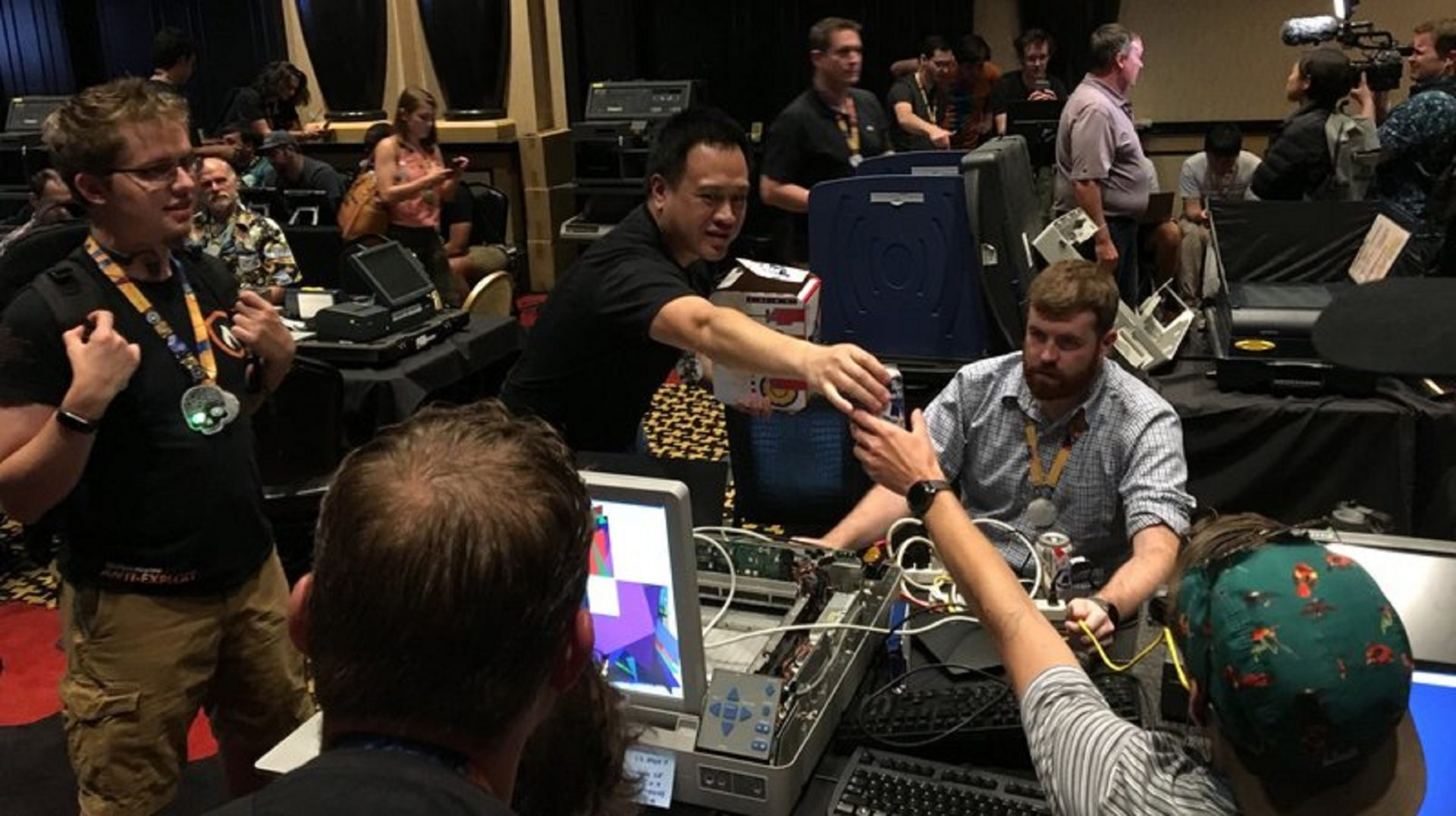 Hackers at this year's Def Con pass out beer as they mess with a voting machine that was used in last year's midterm elections in Virginia.