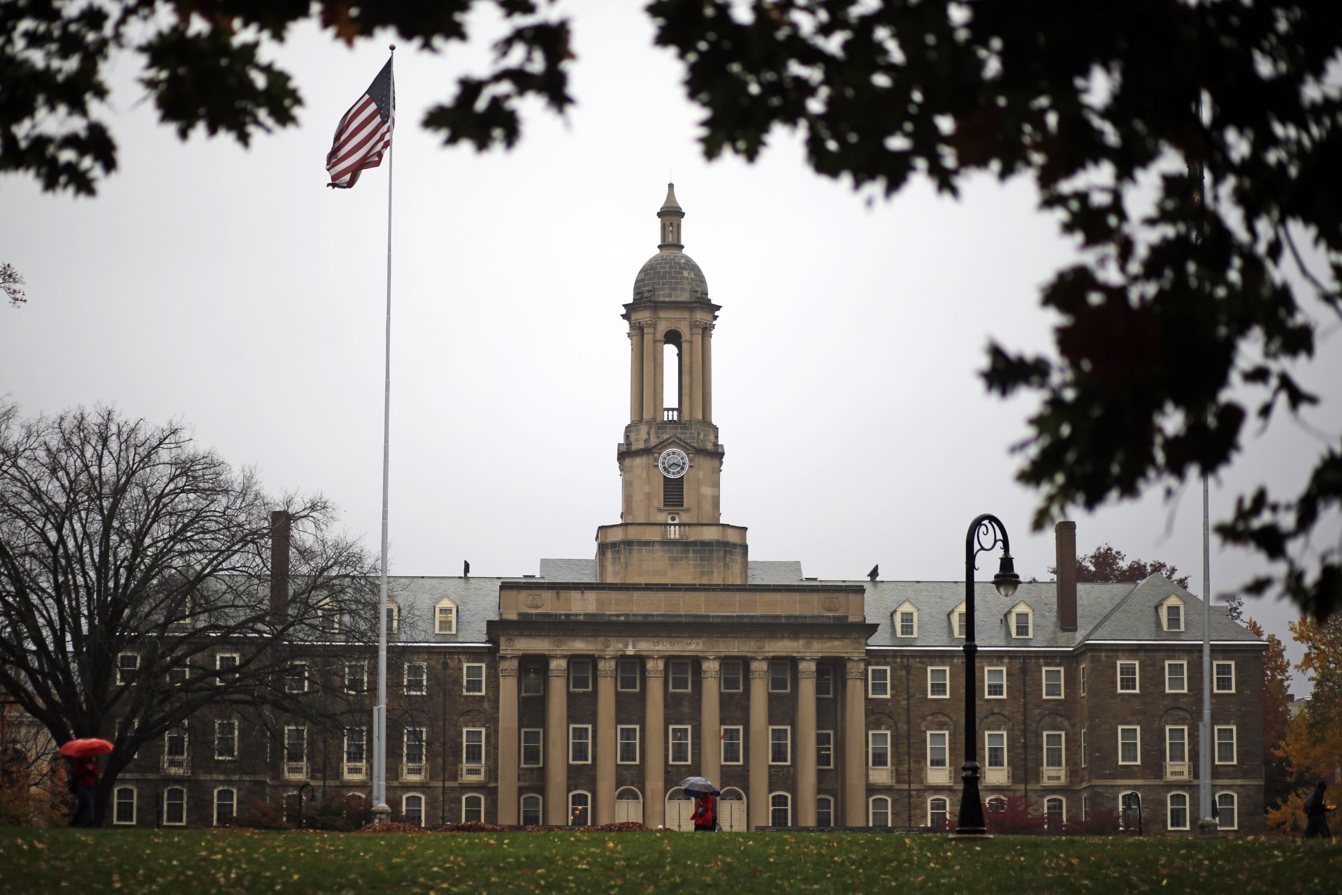 FILE PHOTO: A Penn State student walks in the rain past Old Main on the Penn State main campus in State College, Pa., Wednesday, Oct. 28, 2015.
