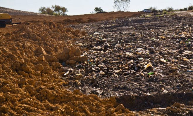 Trash still pokes through at the superfund site in Eastwick in September 2019.