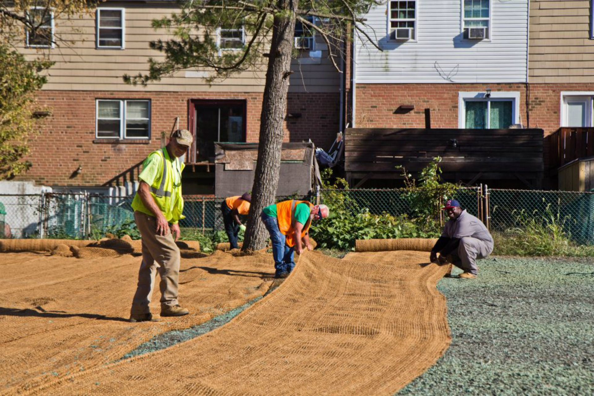 Workers lay coir matting, which is made of coconut fiber that will break down in 2-3 years, but protect hydro seed from water erosion. (Kimberly Paynter/WHYY)