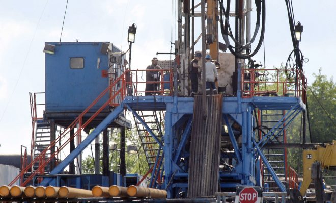 FILE PHOTO: In this June 25, 2012 file photo, a crew works on a gas drilling rig at a well site for shale based natural gas in Zelienople, Pa.