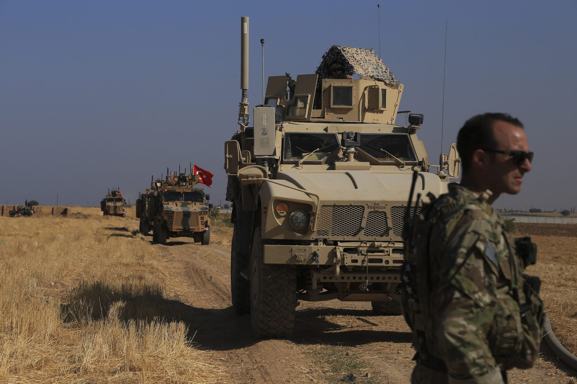 "This Friday, Oct. 4, 2019 file photo, Turkish and American armored vehicles patrol as they conduct joint ground patrol in the so-called ""safe zone"" on the Syrian side of the border with Turkey, near the town of Tal Abyad, northeastern Syria."