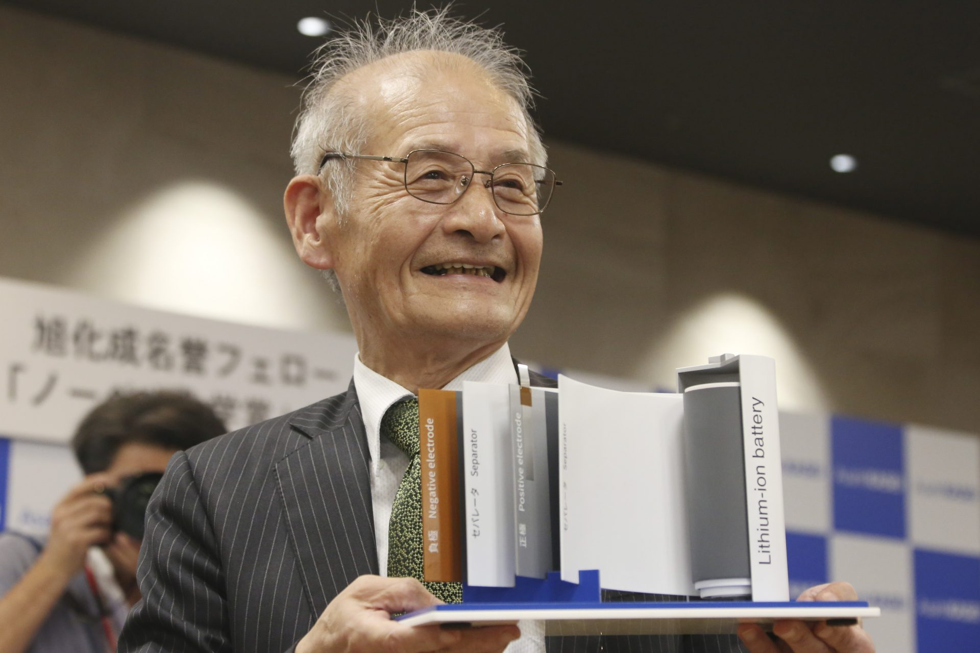 Winner of Nobel Prize in Chemistry Akira Yoshino poses a photo with a model of Lithium-ion battery during a press conference in Tokyo, Wednesday, Oct. 9, 2019. Yoshino is one of the three scientists who have won this year's Nobel Prize in Chemistry for their contributions to lithium-ion batteries, which have reshaped energy storage and transformed cars, mobile phones and many other devices in an increasingly portable and electronic world.