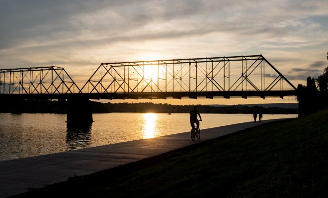 A bicyclist and pedestrians travel next to the Susquehanna River in Harrisburg on Aug. 19, 2019.