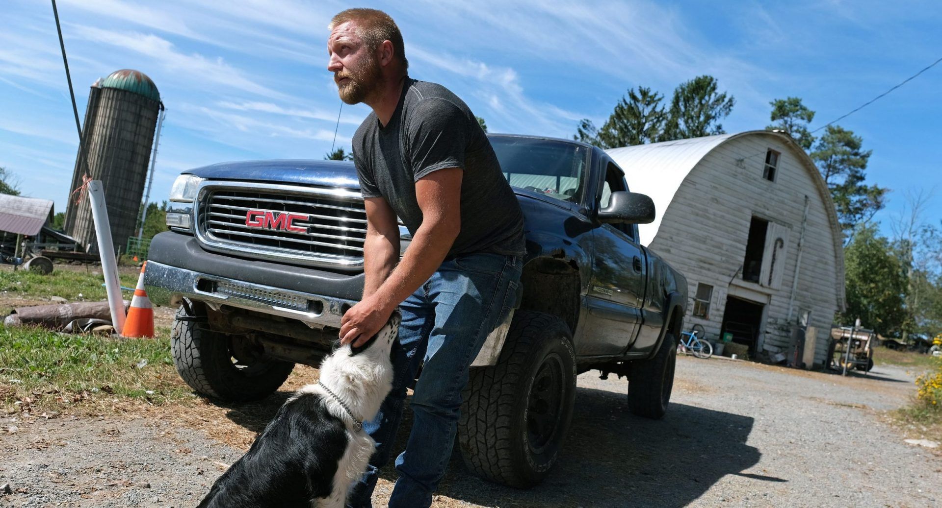 Grain farmer Jesse Poliskiewicz pets a dog while visiting his father's farm Sept. 20, 2019, in Upper Mount Bethel Township, Pennsylvania.