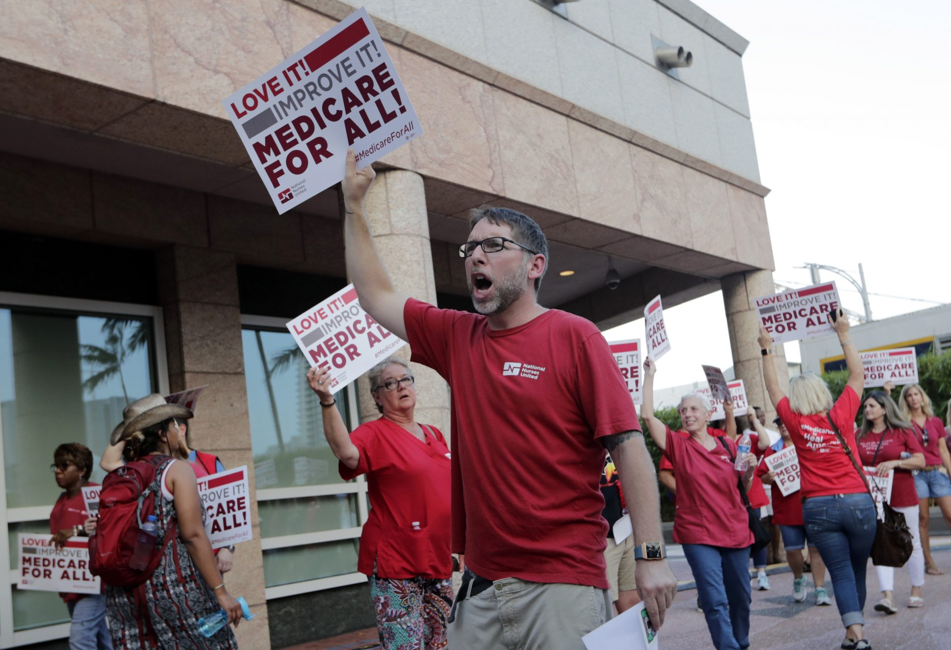 People with National Nurses United march in support of medicare for all, outside of the Knight Concert Hall at the Adrienne Arsht Center for the Performing Arts of Miami-Dade County, where a Democratic presidential debate is taking place, Wednesday, June 26, 2019, in Miami.