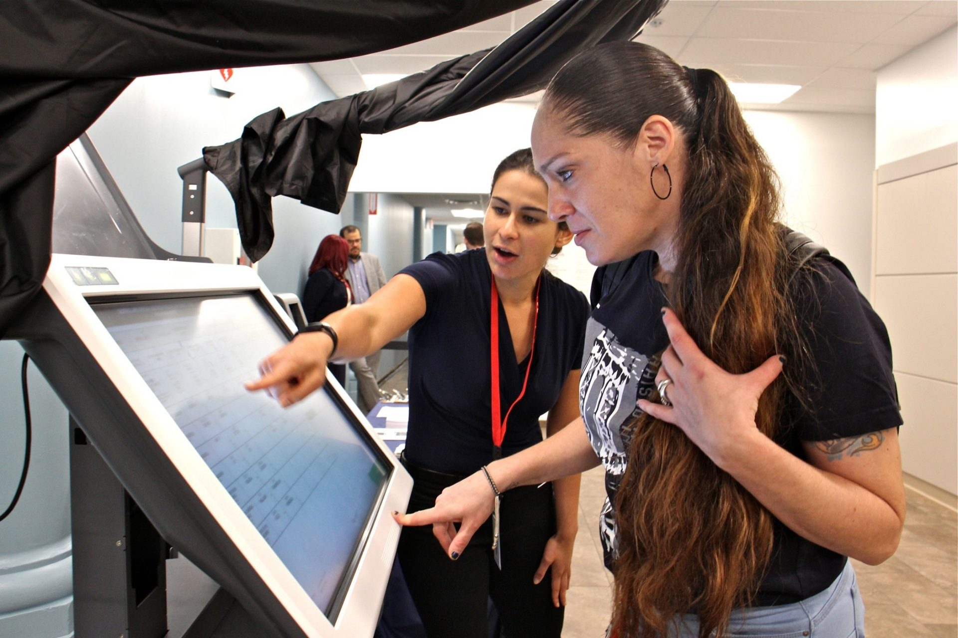 Diane Duffin learns how to use a voting machine with the help of Michelle Montalvo of the City Commissioners Office. Duffin registered to vote for the first time after learning that a conviction did not prevent her from voting in Pennsylvania.