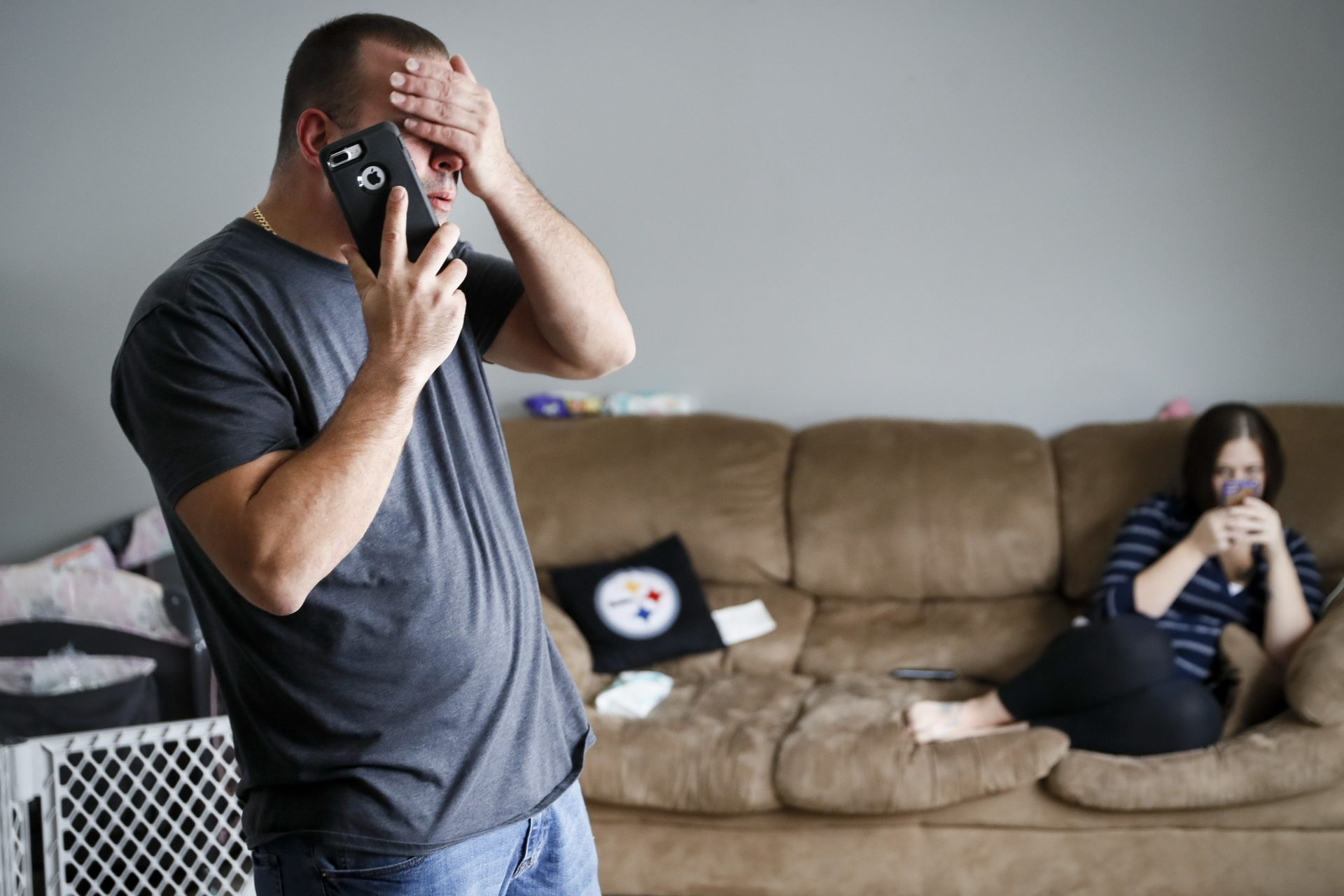 FILE PHOTO: In this Nov. 28, 2018, file photo Tom Wolikow, a General Motors employee who is currently laid-off, left, takes a phone call at home alongside his fiance Rochelle Carlisle in Warren, Ohio. An economic renaissance in the industrial Midwest promised by President Donald Trump has suffered in recent weeks in ways that could be problematic for Trump's 2020 re-election.
