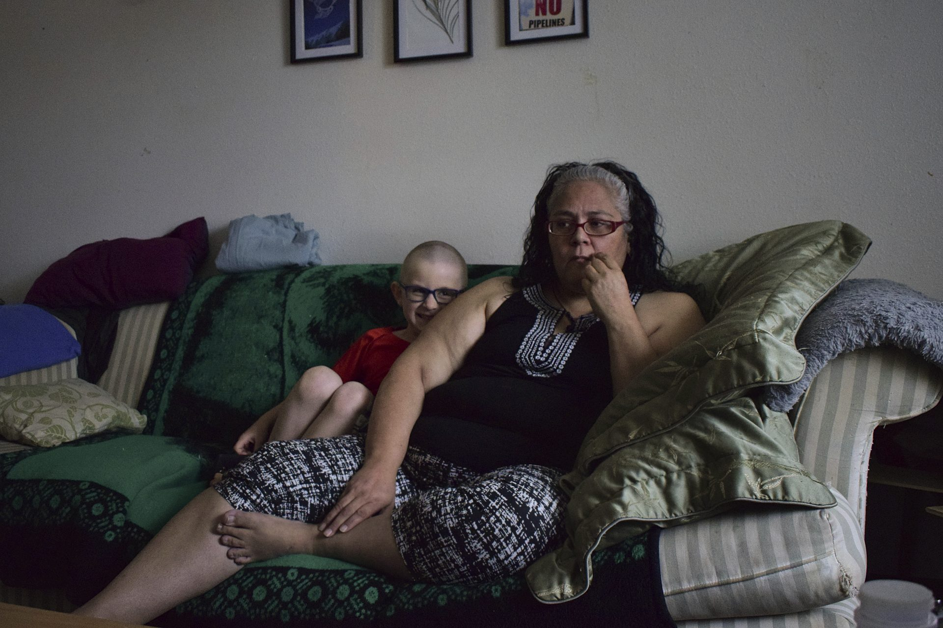 Leona Peterson and her son, Wayne, 6, sit in their home in Prince Rupert, British Columbia, Canada. When Peterson moved into the subsidized Indigenous housing complex with her family, a neighbor warned her about the poor quality of the drinking water.