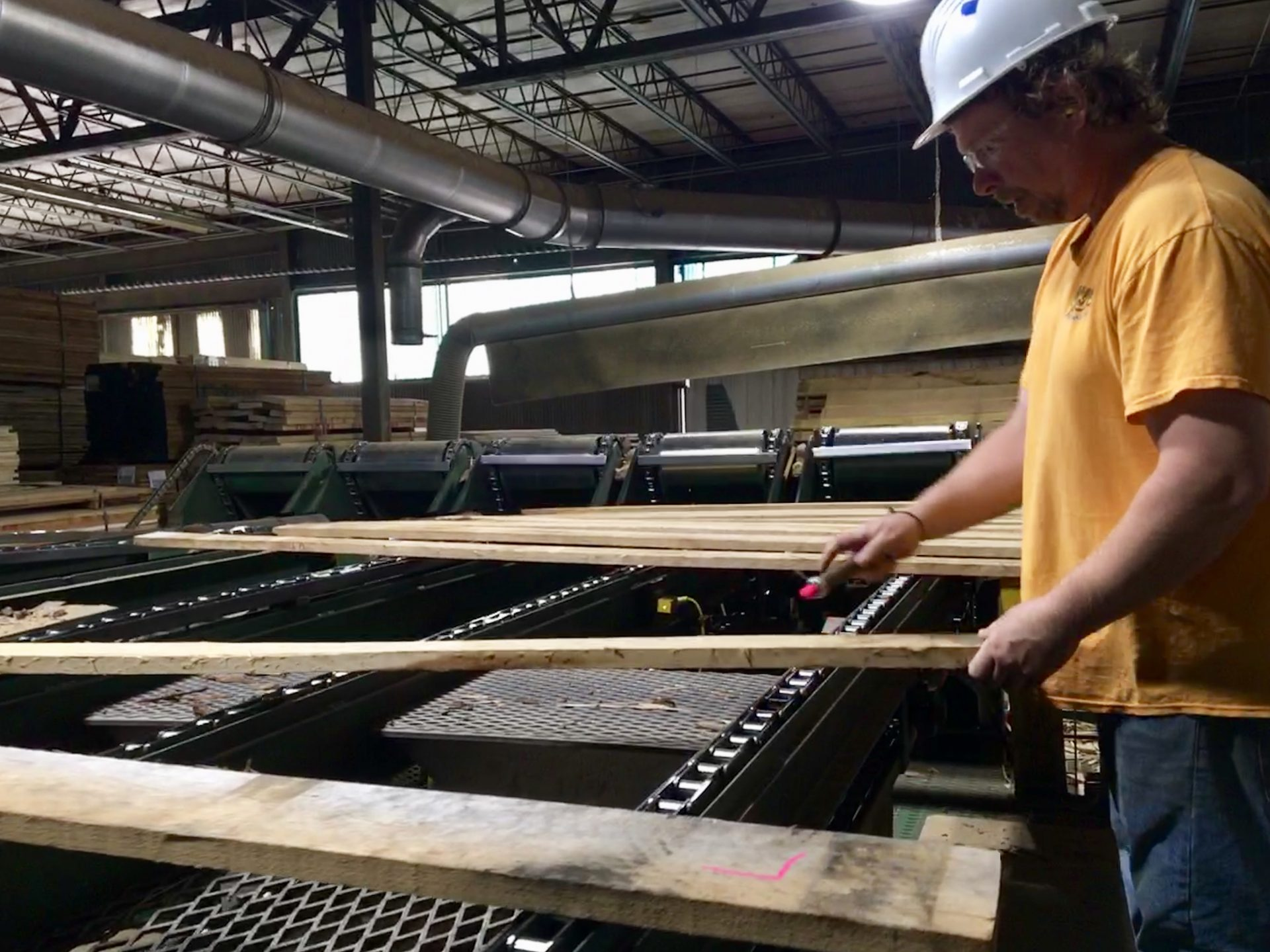 An employee at Collins Hardwood in Kane, Pennsylvania, sorts and marks the wood. The ongoing trade war with China is taking a toll on the hardwood industry in Pennsylvania and nationally.