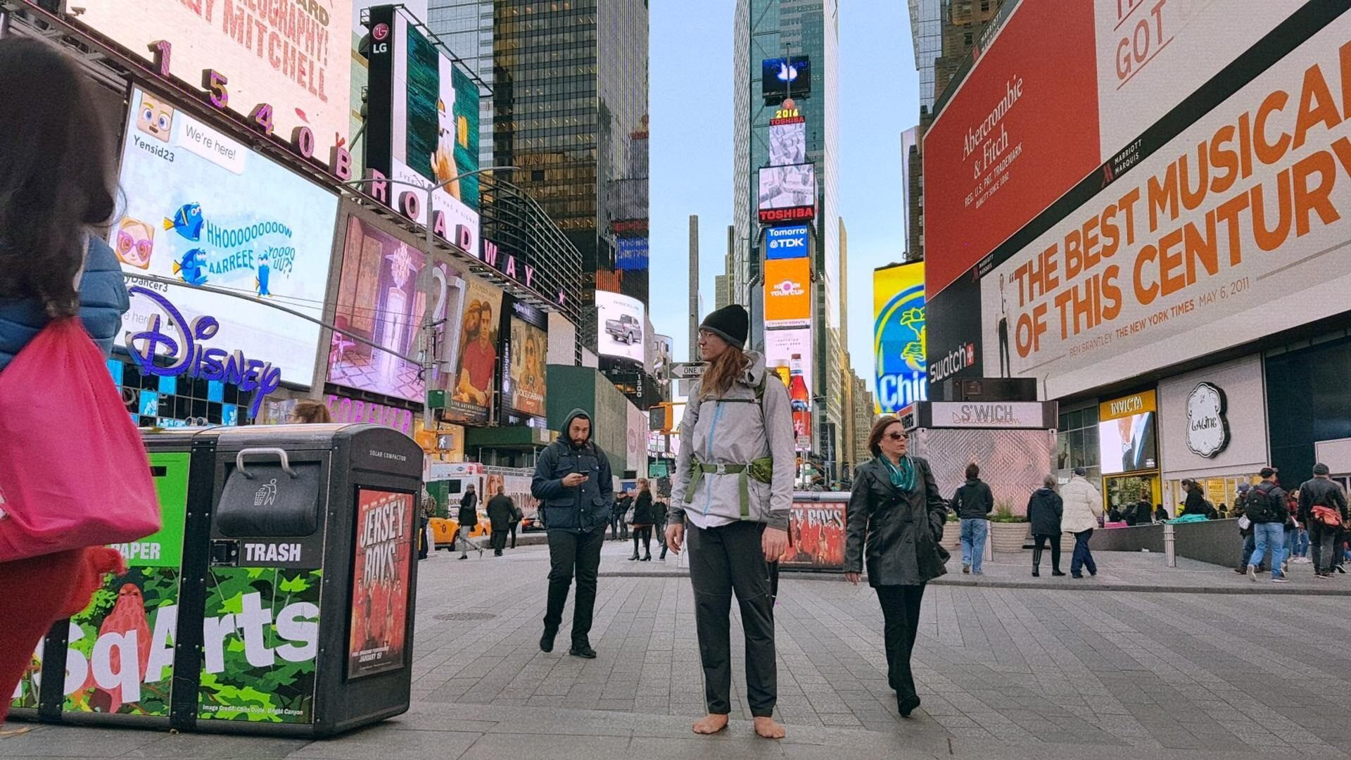 Barefoot in Times Square: Mark Baumer pauses partway into his trip.