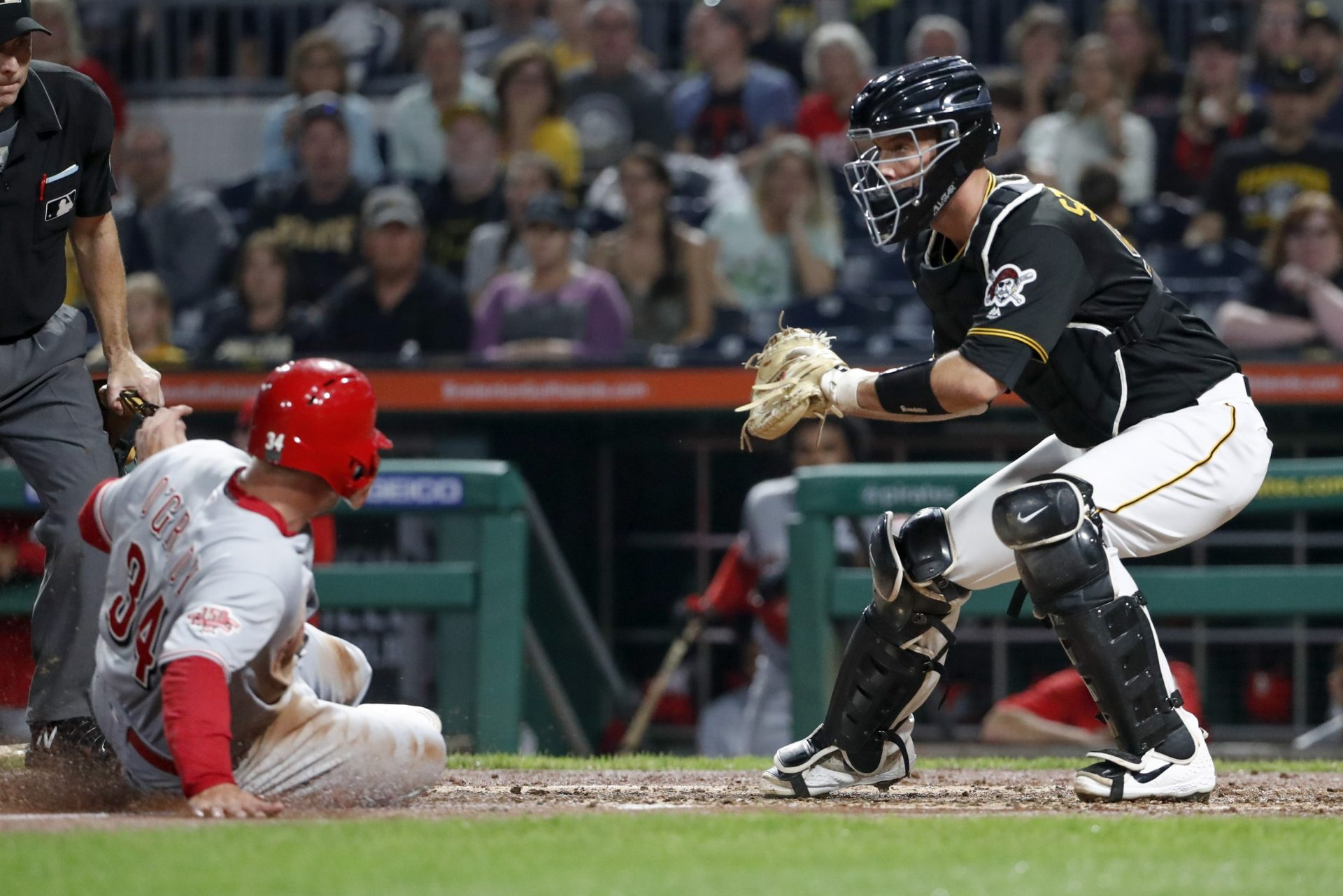 Pittsburgh Pirates catcher Jacob Stallings, right, gets the force out on Cincinnati Reds' Brian O'Grady at home on a bases loaded ground ball by Aristides Aquino in the third inning of a baseball game, Saturday, Sept. 28, 2019, in Pittsburgh.