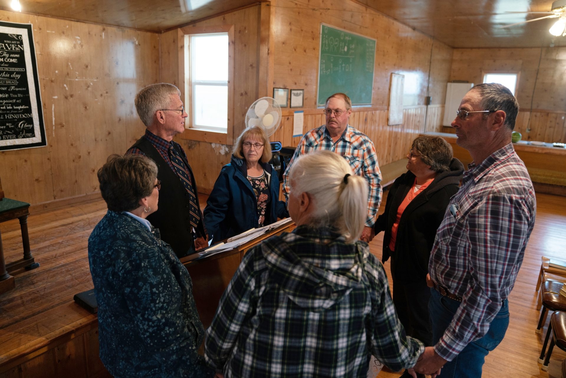 Ranchers gather with traveling pastor Hal DeBoer for a religious service at First Creek Community Hall.