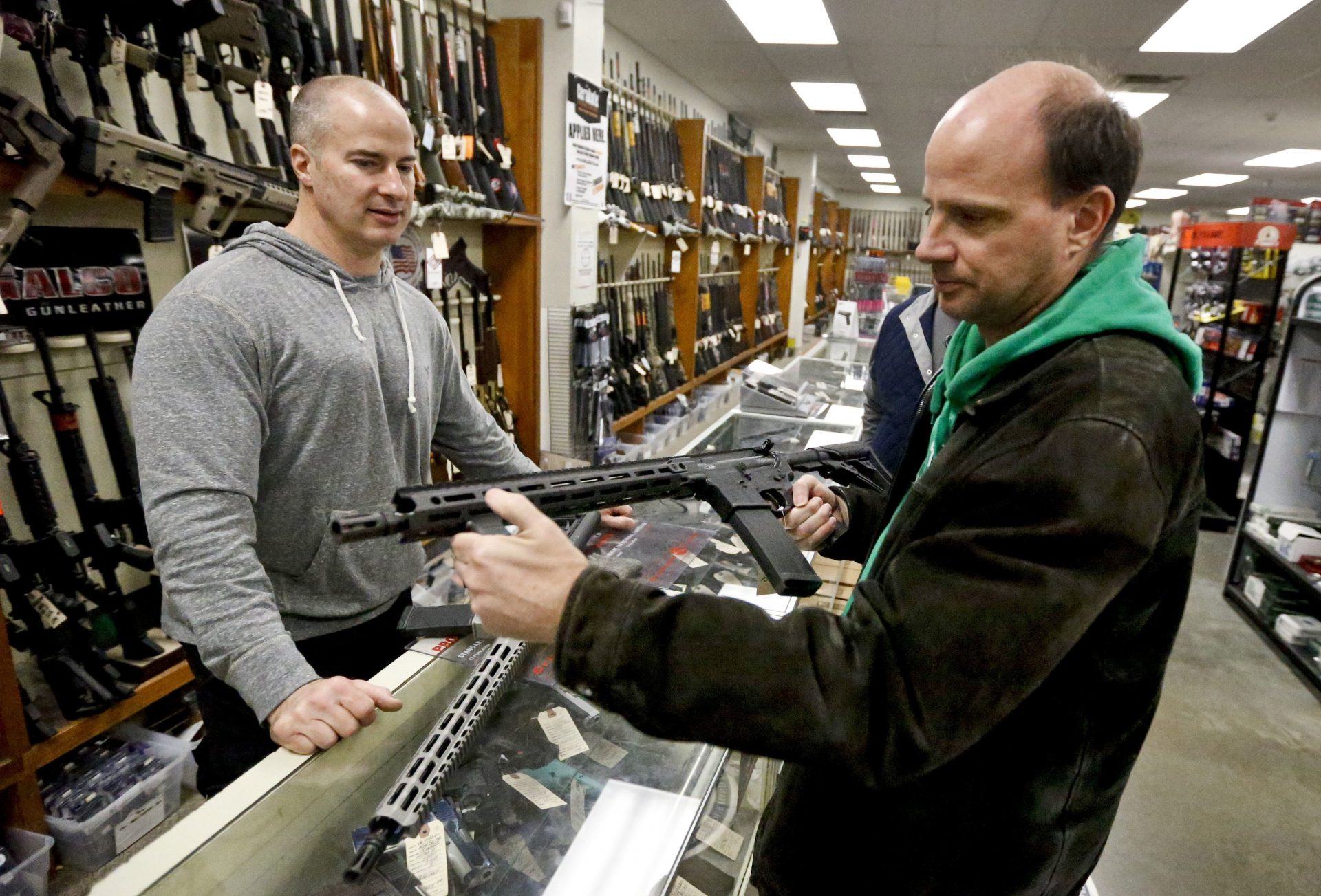 Wes Morosky, owner of Duke's Sport Shop. left, helps Ron Detka as he shops for a rifle on Friday, March 2, 2018, at his store in New Castle. Morosky said business has gone up recently, but that's thanks to the annual infusion of tax refund checks. Sales of firearms slowed dramatically after the election of President Donald Trump in 2016 allayed fears of a Democratic crackdown on gun owners. That trend continues, even with talk of gun control in Congress following the massacre of 17 people at a Florida high school last month.