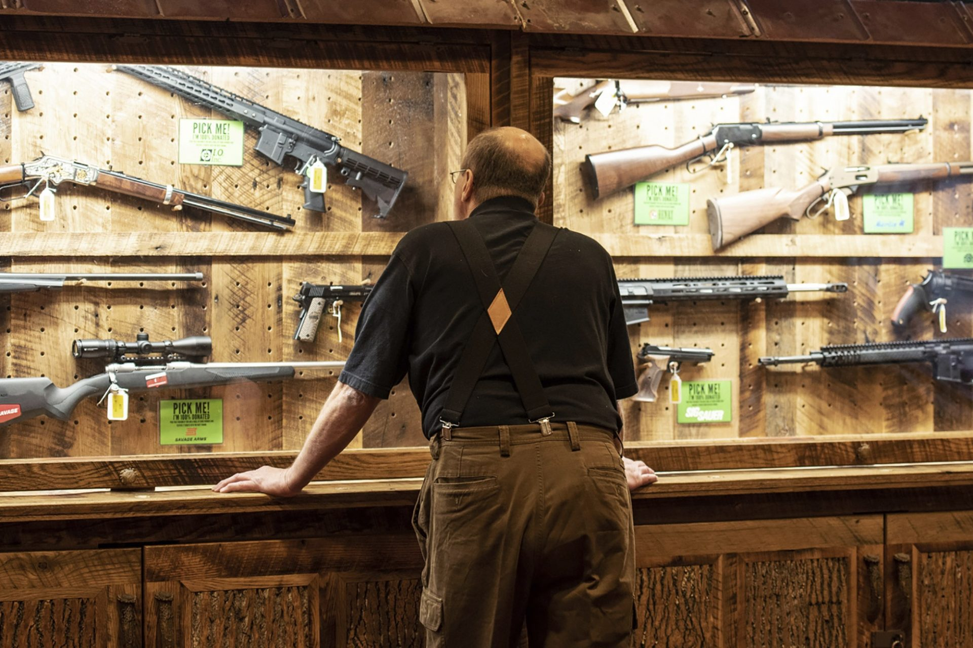 FILE - In this April 25, 2019, file photo, a man looks at cases of firearms in the halls of the Indianapolis Convention Center where the National Rifle Association will be holding its 148th annual meeting in Indianapolis. The number of background checks conducted by federal authorities is on pace to break a record by the end of this year.