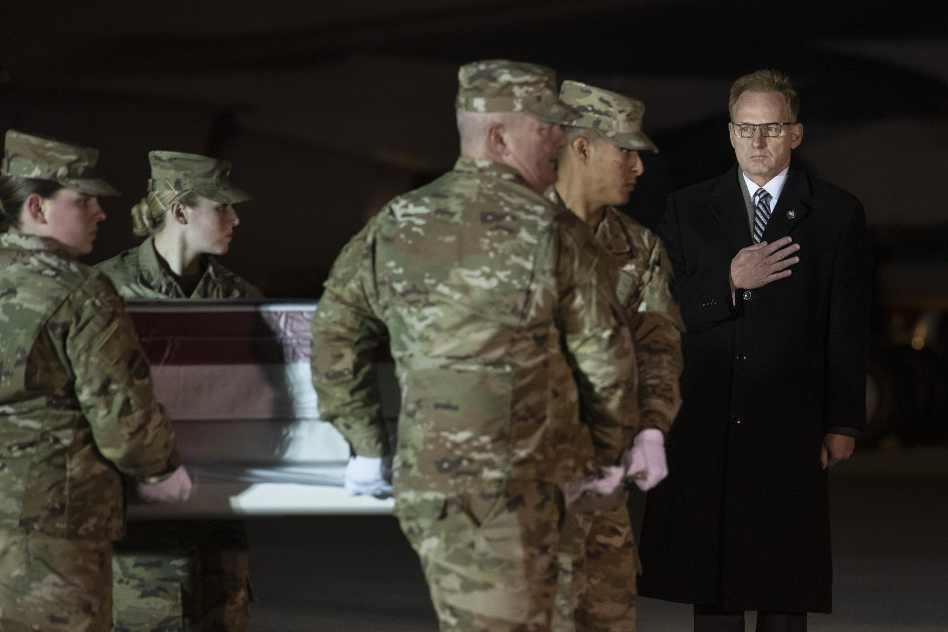 Acting Navy Secretary Thomas Modly, right, looks on as an Air Force carry team moves a transfer case containing the remains of Navy Ensign Joshua Watson on Sunday, Dec. 8, 2019, at Dover Air Force Base, Del. A Saudi gunman killed three people including 23-year-old Watson, a recent graduate of the U.S. Naval Academy from Enterprise, Ala., in a shooting at Naval Air Station Pensacola in Florida.