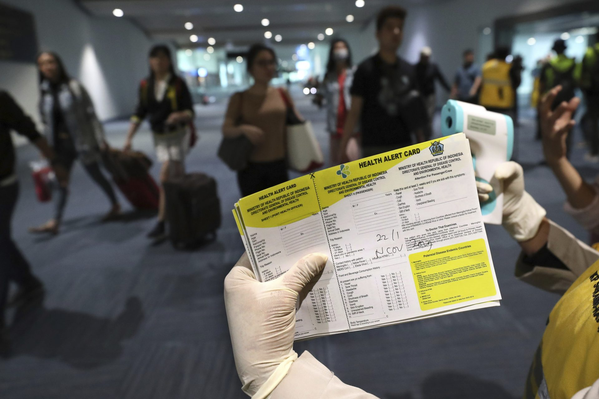 A health official holds a health alert card at the Soekarno-Hatta International Airport in Tangerang, Indonesia, Wednesday, Jan. 22, 2020. Indonesia is screening travelers from overseas for a new type of coronavirus as fears spread about a mysterious infectious disease after its first death reported in China.