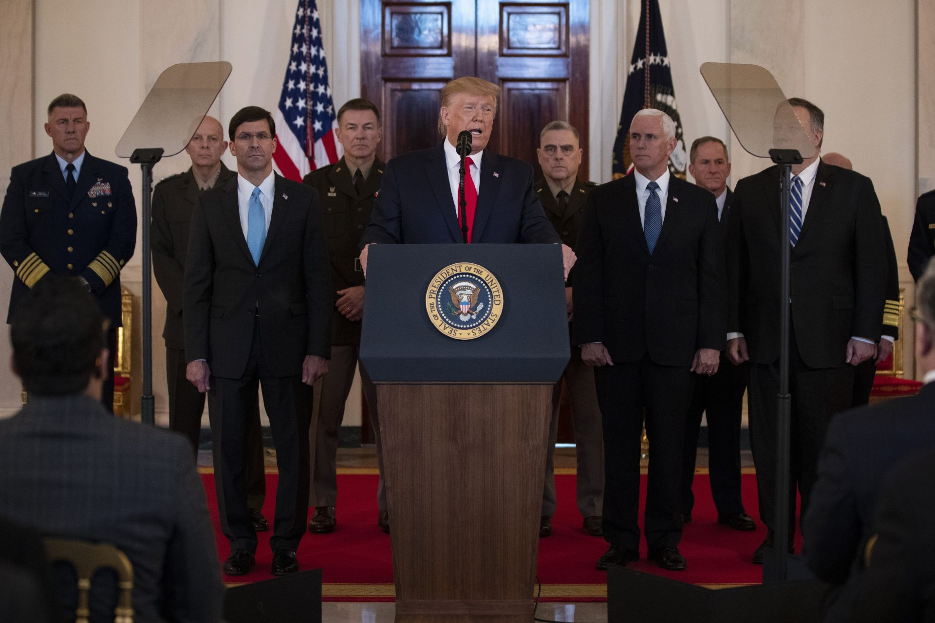 President Donald Trump addresses the nation from the White House on the ballistic missile strike that Iran launched against Iraqi air bases housing U.S. troops, Wednesday, Jan. 8, 2020, in Washington, as Secretary of Defense Mark Esper, Chairman of the Joint Chiefs of Staff Gen. Mark Milley, Vice President Mike Pence, and Secretary of State Mike Pompeo, and others look on.