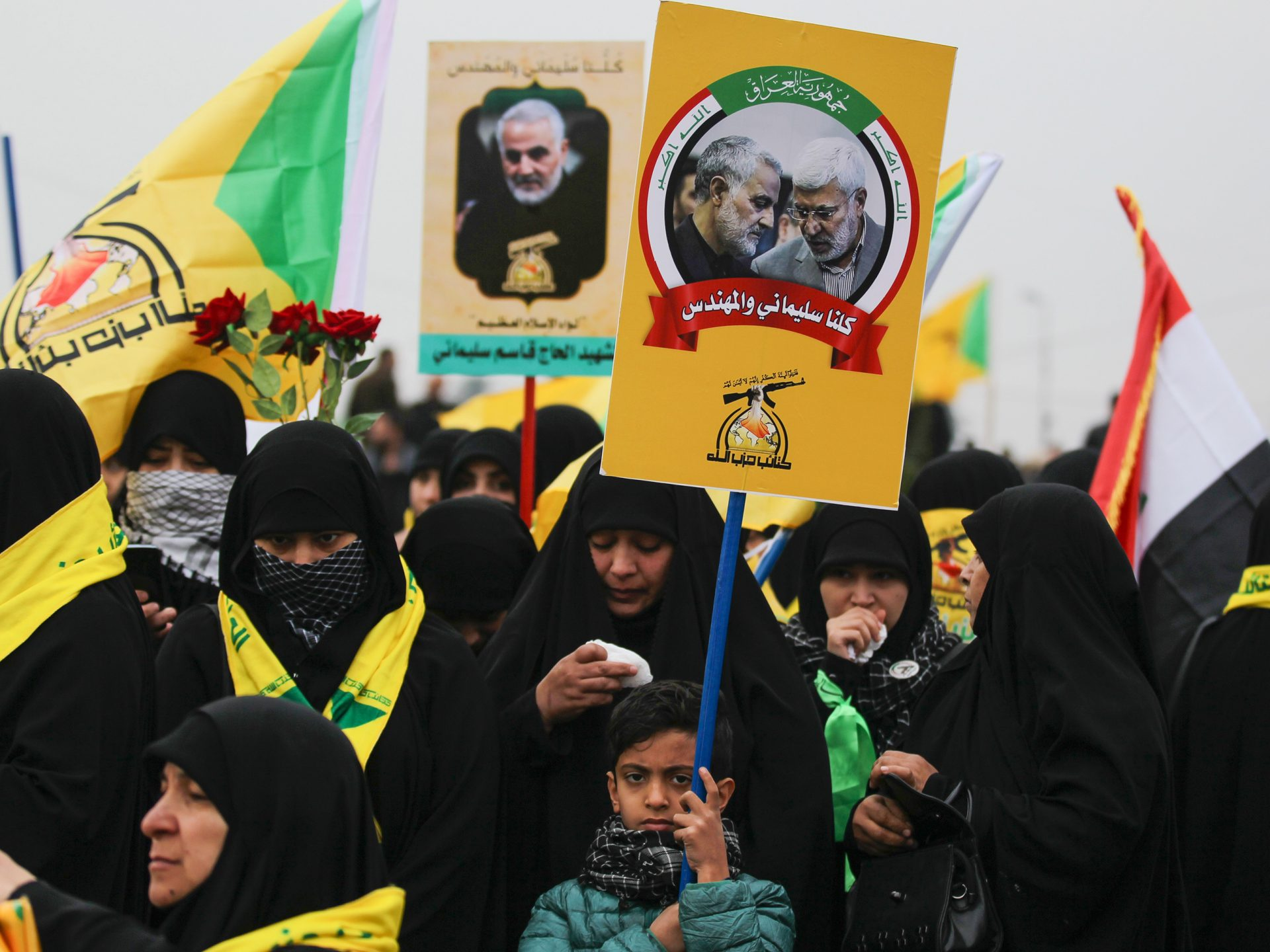 """Demonstrators hold aloft portraits of Iraqi paramilitary chief Abu Mahdi al-Muhandis and Iranian military leader Qassem Soleimani during the funeral procession Saturday in Baghdad. The crowd of thousands chanted """"Death to America"""" at times."""