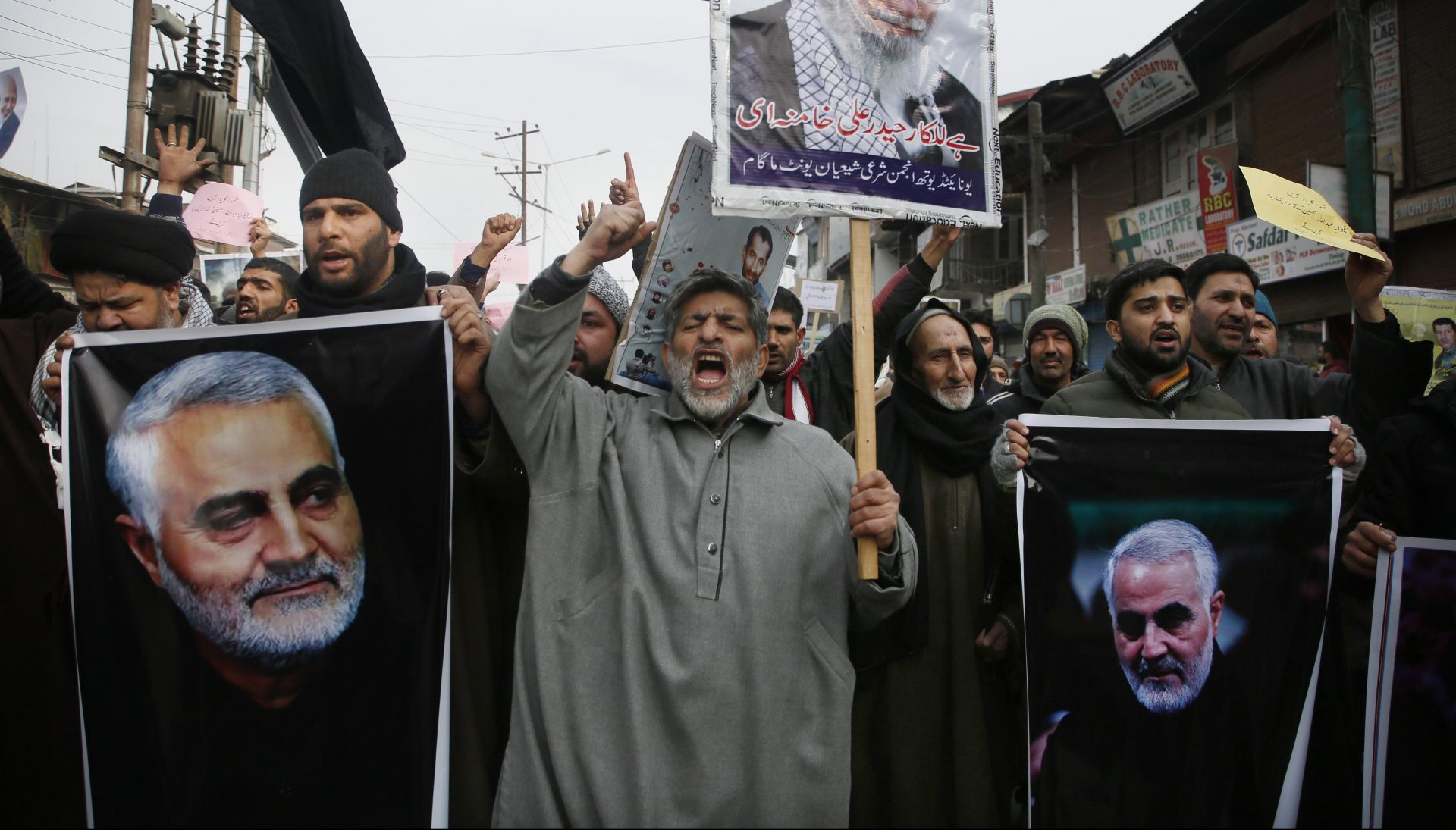 Kashmiri Shiite Muslims shout anti American and anti Israel slogans during a protest against U.S. airstrike in Iraq that killed Iranian Revolutionary Guard Gen. Qassem Soleimani, seen in the photographs, at Magam 37 kilometers (23 miles) north of Srinagar, Indian controlled Kashmir, Friday, Jan. 3, 2020. The killing of Iran's top military commander Gen. Qassem Soleimani triggered several anti-U.S. protests in Indian-controlled Kashmir, the protesters also shut down shops and businesses in Magam and Budgam towns in south Kashmir.