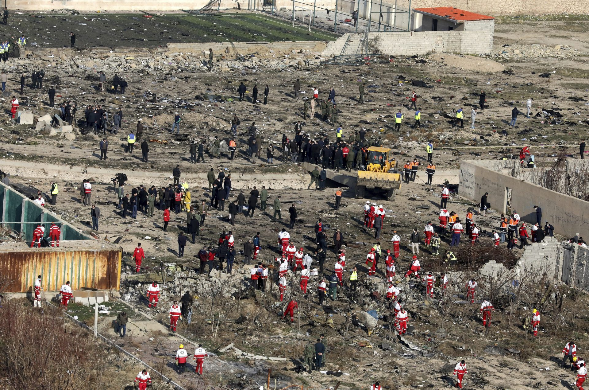 Rescue workers search the scene where an Ukrainian plane crashed in Shahedshahr, southwest of the capital Tehran, Iran, Wednesday, Jan. 8, 2020. A Ukrainian passenger jet carrying 176 people crashed on Wednesday, just minutes after taking off from the Iranian capital's main airport, turning farmland on the outskirts of Tehran into fields of flaming debris and killing all on board.