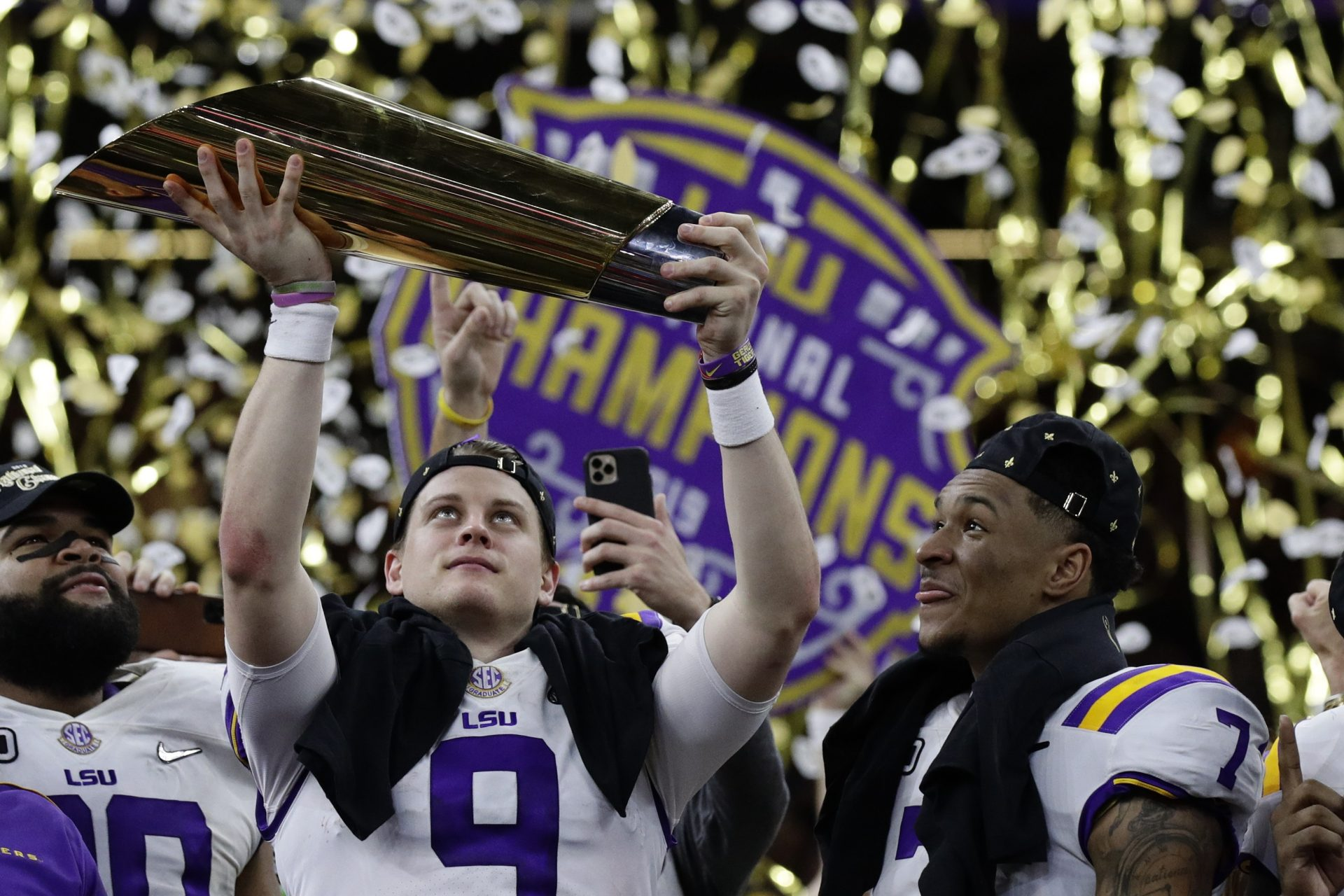 LSU quarterback Joe Burrow holds the trophy as safety Grant Delpit looks on after a NCAA College Football Playoff national championship game against Clemson, Monday, Jan. 13, 2020, in New Orleans. LSU won 42-25.
