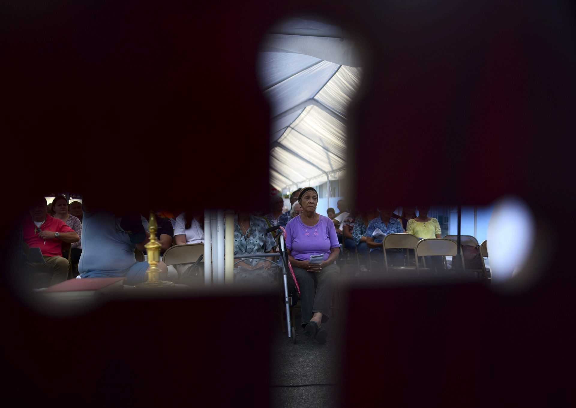 Seen through the cut-out shape of a cross on a priest's chair, a woman attends an outdoor Mass under a tent set up near the Immaculate Concepcion Catholic Church, which sustained earthquake-related damaged earlier in the week, following a magnitude 5.9 quake earlier in the day in Guanica, Puerto Rico, Saturday, Jan. 11, 2020. The morning quake caused further damage along the island's southern coast, where previous recent quakes have toppled homes and schools.