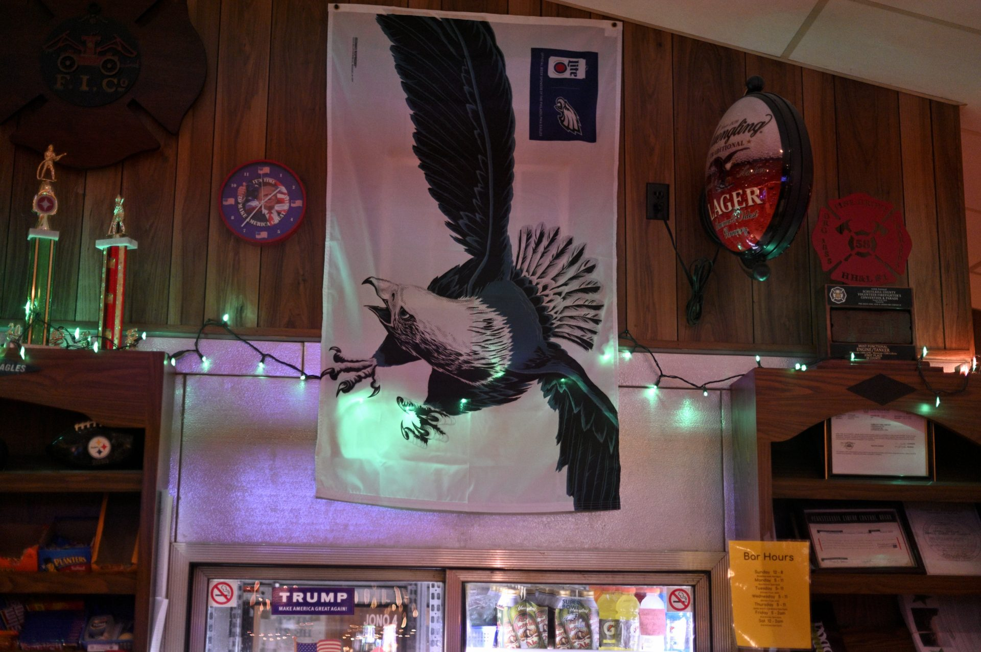 A sticker and clock in suport of President Donald Trump, as well as a large Eagles flag are found behind the bar of the Social Quarters of the Landingville Community Fire Company, in Landingville, PA, on December 15, 2019.