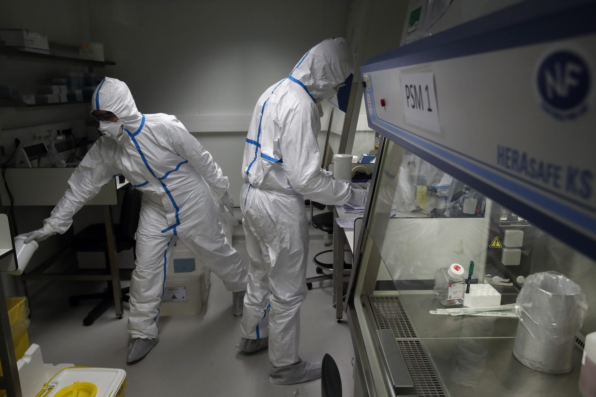 French lab scientists in hazmat gear inserting liquid in test tube manipulate potentially infected patient samples at Pasteur Institute in Paris, Thursday, Feb. 6, 2020. Scientists at the Pasteur Institute developed and shared a quick test for the new virus that is spreading worldwide, and are using genetic information about the coronavirus to develop a potential vaccine and treatments.