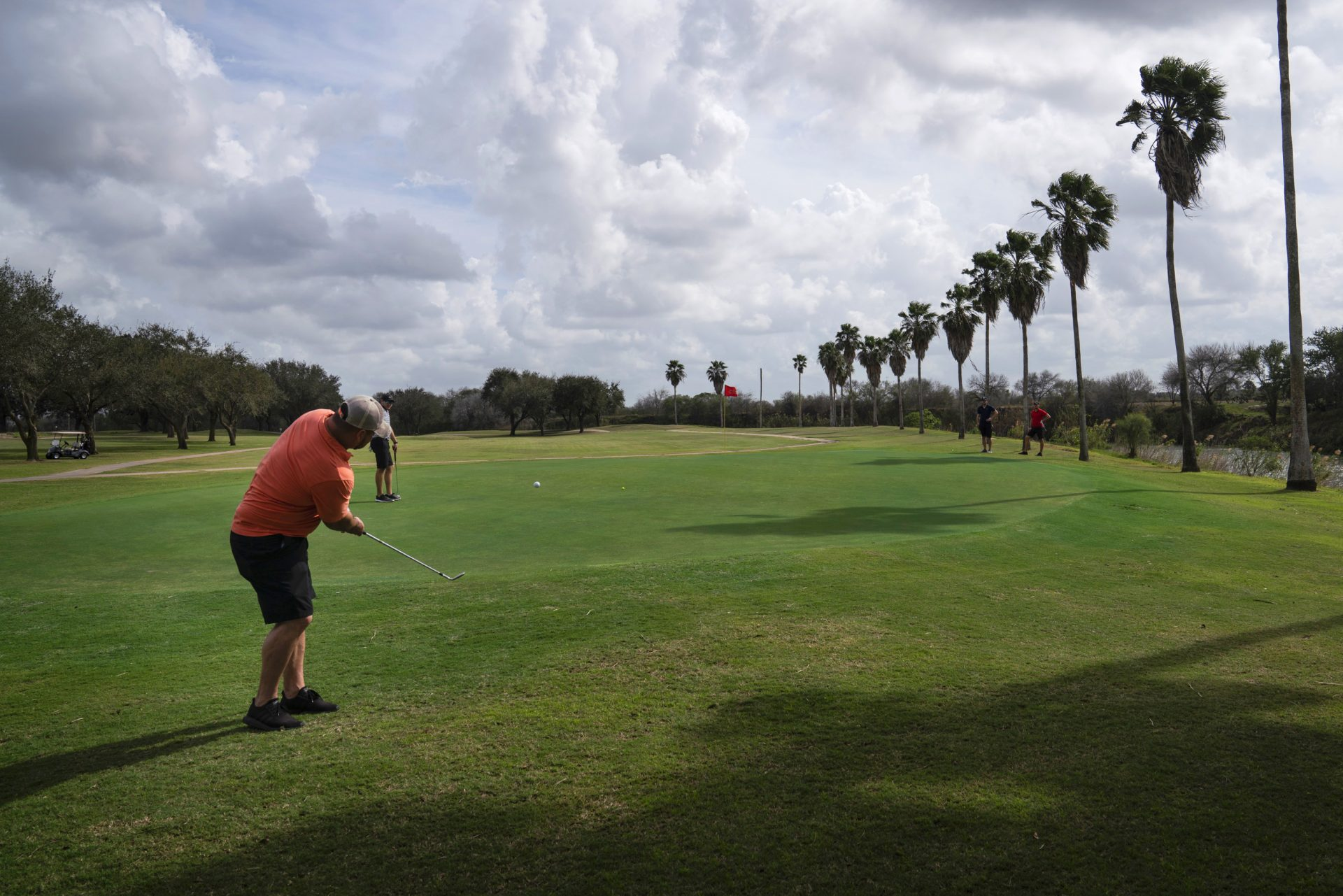 Memo Ibarra hits the ball at River Bend Resort & Golf Club in Brownsville, Texas. The 18-hole golf course would have 15 of them on the south side of Trump's proposed border wall.