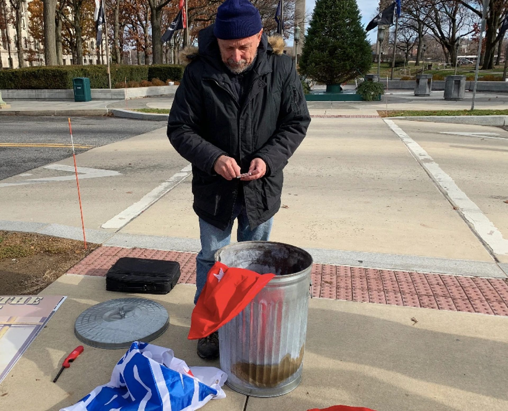 Citizen activist Gene Stilp prepares to strike a match to set one of his Trump campaign flags on fire outside the Pa. Capitol on Dec. 5, 2019. On Tuesday, a Harrisburg district judge found him not guilty of violating a city burn ban.
