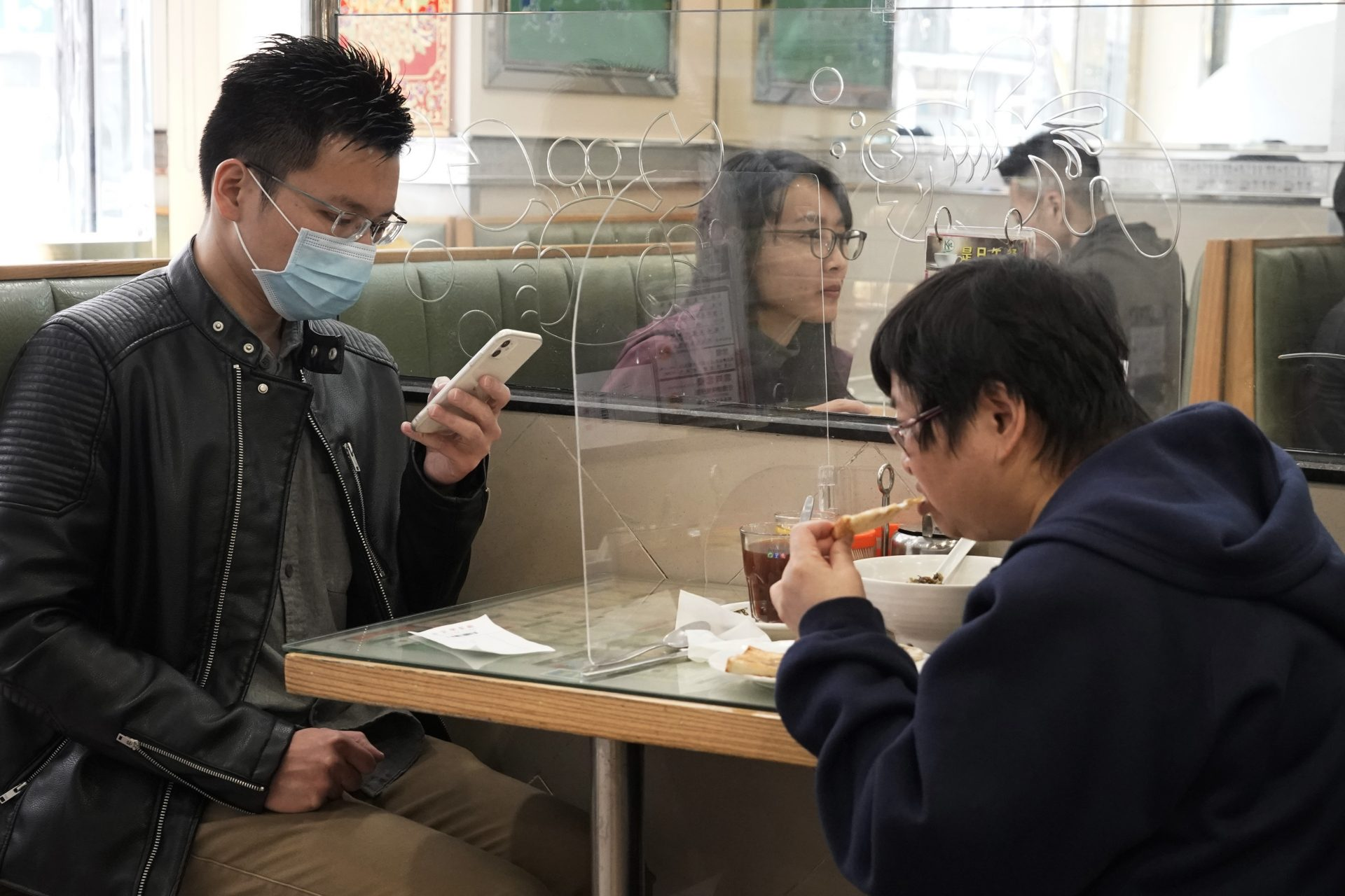 Customers have lunch with a transparent plastic panel setup on the table to isolate each other to prevent spreading of the coronavirus in Hong Kong, Wednesday, Feb. 12, 2020. China's ruling Communist Party needs to make a politically fraught decision: Admit a viral outbreak isn't under control and cancel this year's highest-profile official event. Or bring 3,000 legislators to Beijing next month and risk fueling public anger at the government's handling of the disease.