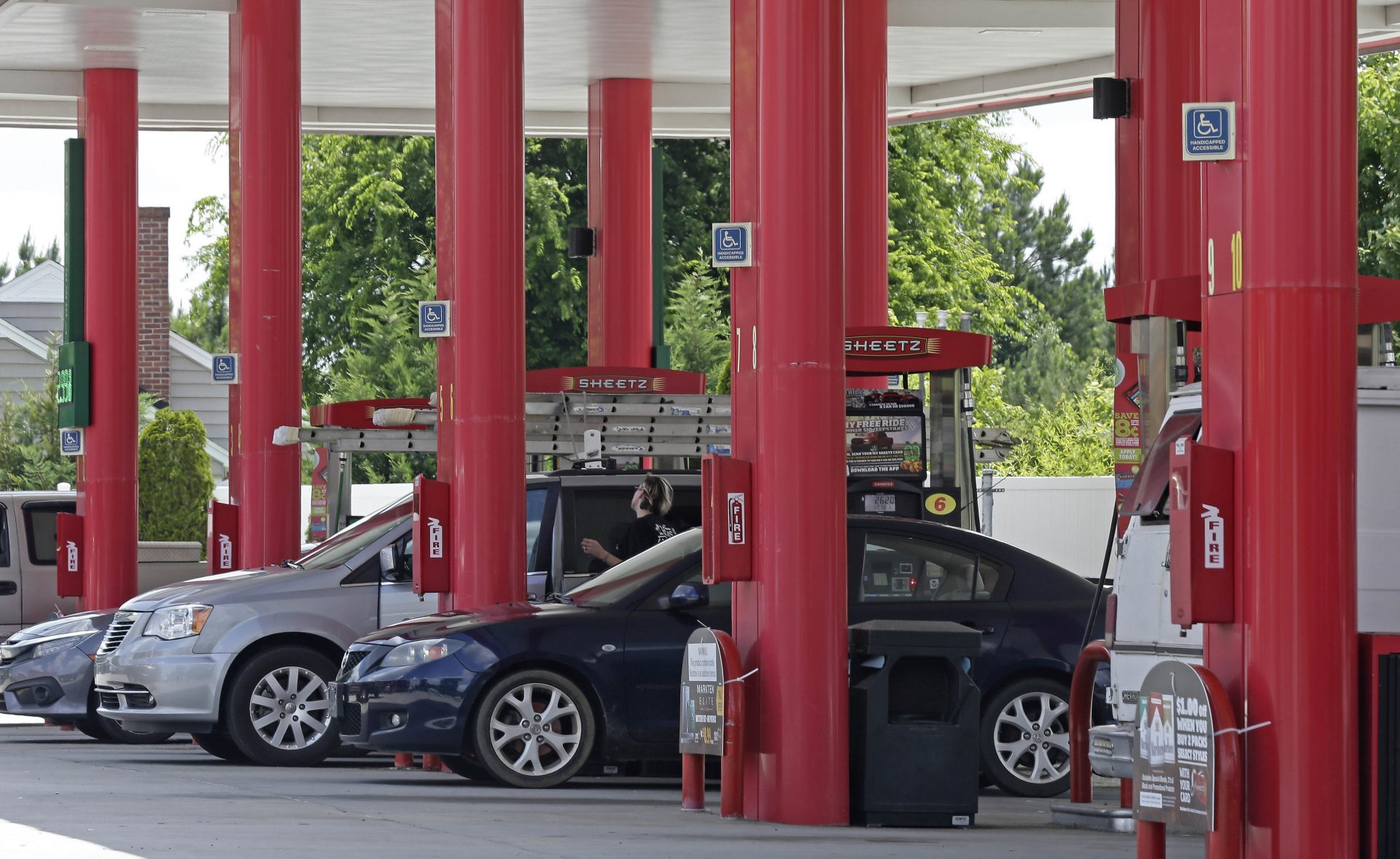 In this photo taken Thursday, June 14, 2018 cars are fueled at Sheetz along the Interstate 85 and 40 corridor near Burlington, N.C.