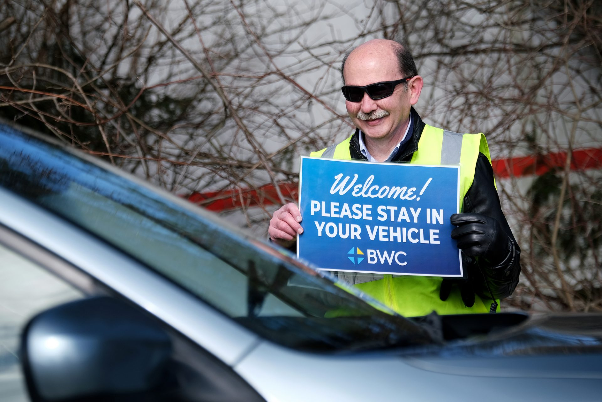 Pastor Dwight Addington holds a sign while parishioners arrive as Bethany Wesleyan Church holds Sunday worship service at Becky's Drive-In in Northampton County
