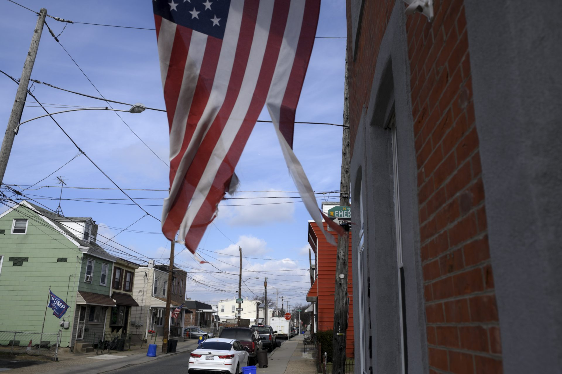 A torn American flag waves on a residential street in Bridesburg.