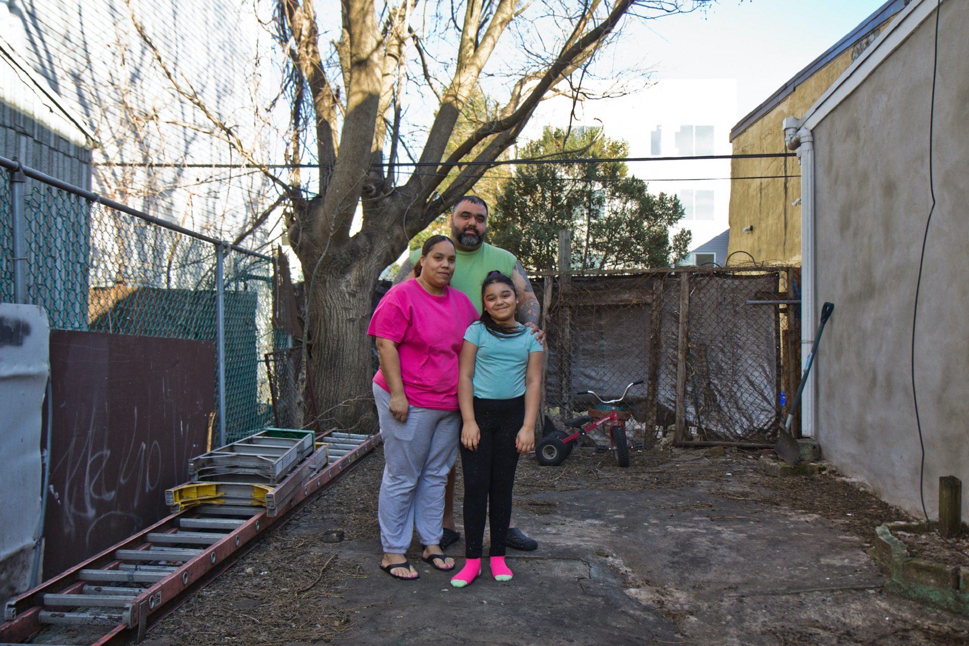 Adamarie Baez and Daniel Ortiz with their ten year-old daughter Kaylee in the lot next to their home they've maintained and gardened in for years.