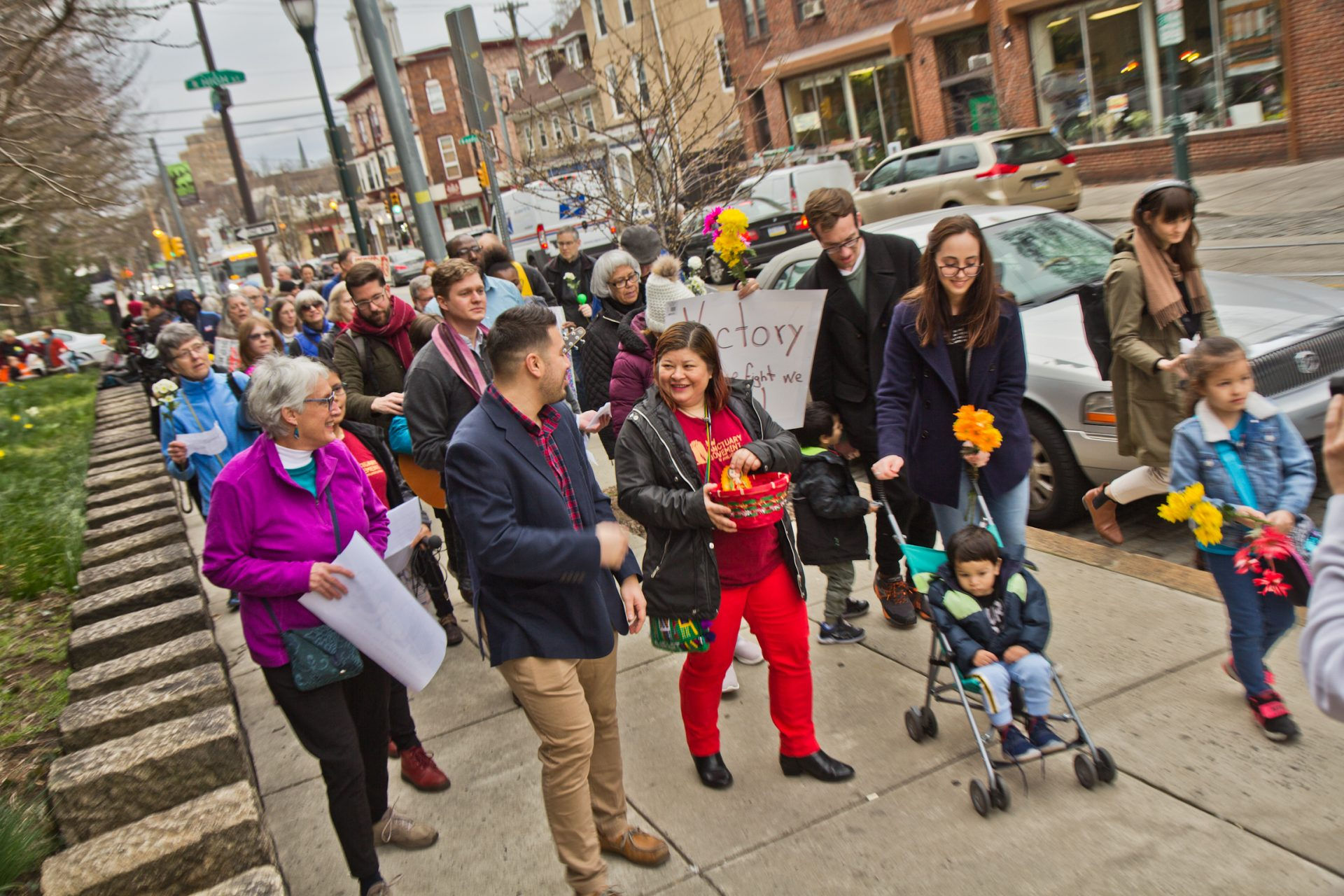 Suyapa Reyes and members of the First United congregation march to the Germantown Mennonite church where Carmela Apolonio Hernandez, another mother living in sanctuary, has called home for the past two years.