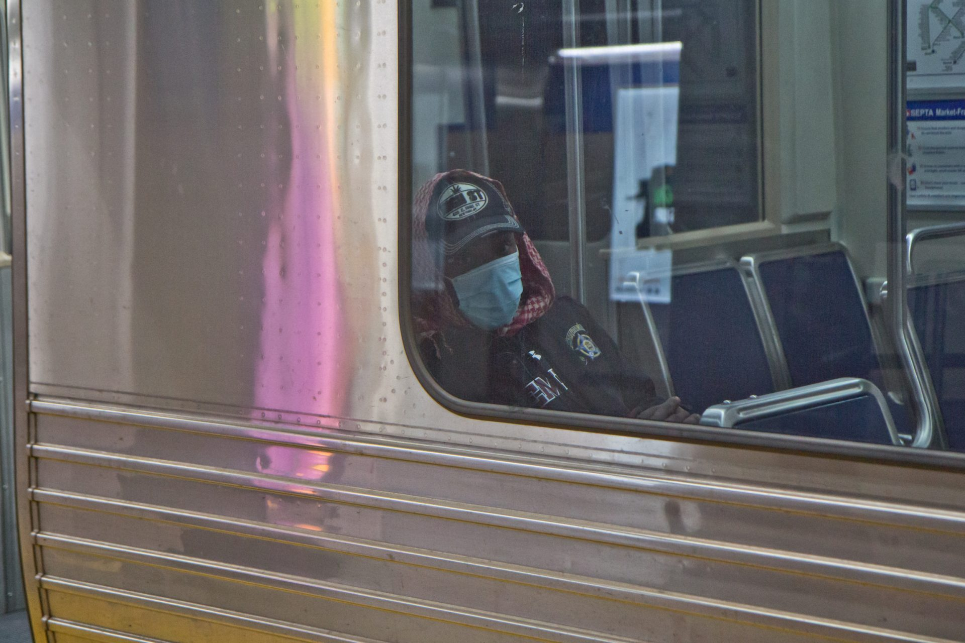 A SEPTA rider dons a surgical mask.