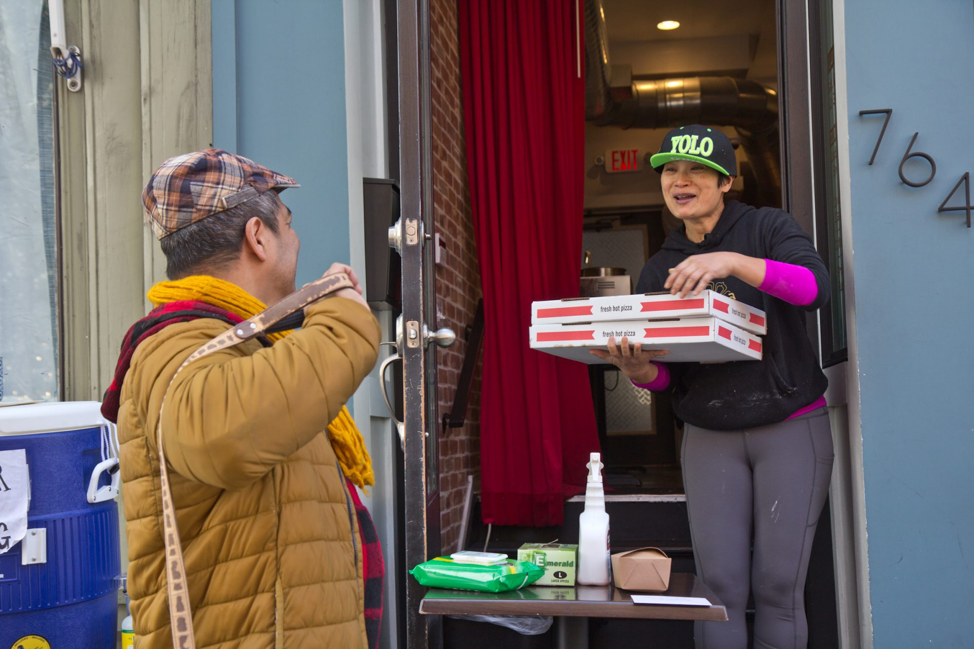 Kalaya owner Nok Suntaranon (right) hands out donated pizza to community members in need.