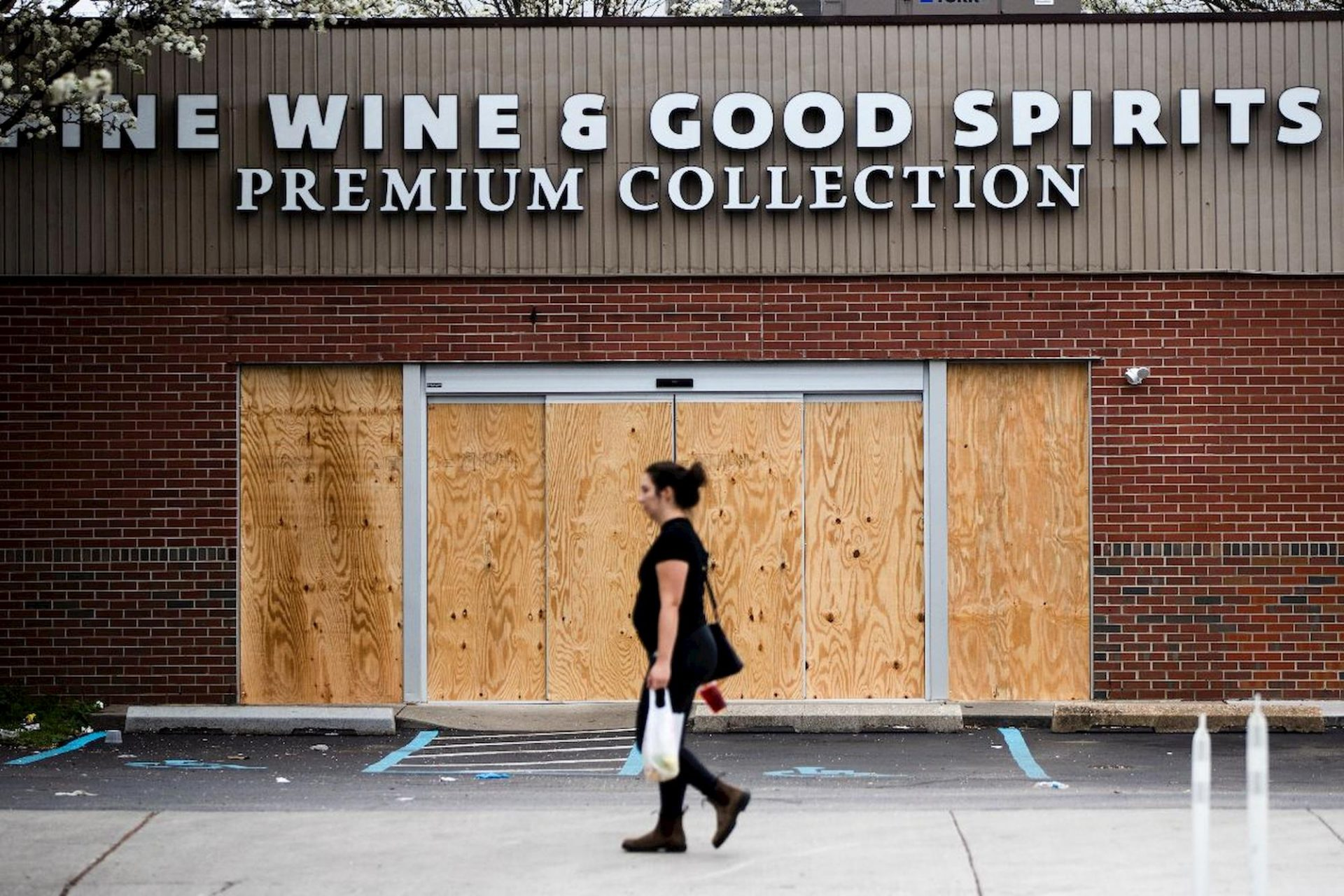 A pedestrian walks past a boarded up Wine and Spirits store in Philadelphia, Friday, March 20, 2020.
