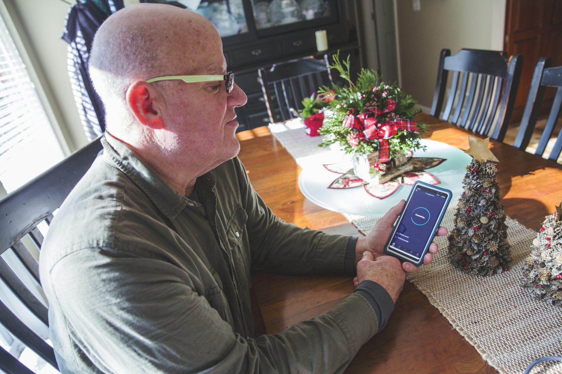Tom Bracken, a volunteer at the cooperative, tests the DSL internet speeds at home.