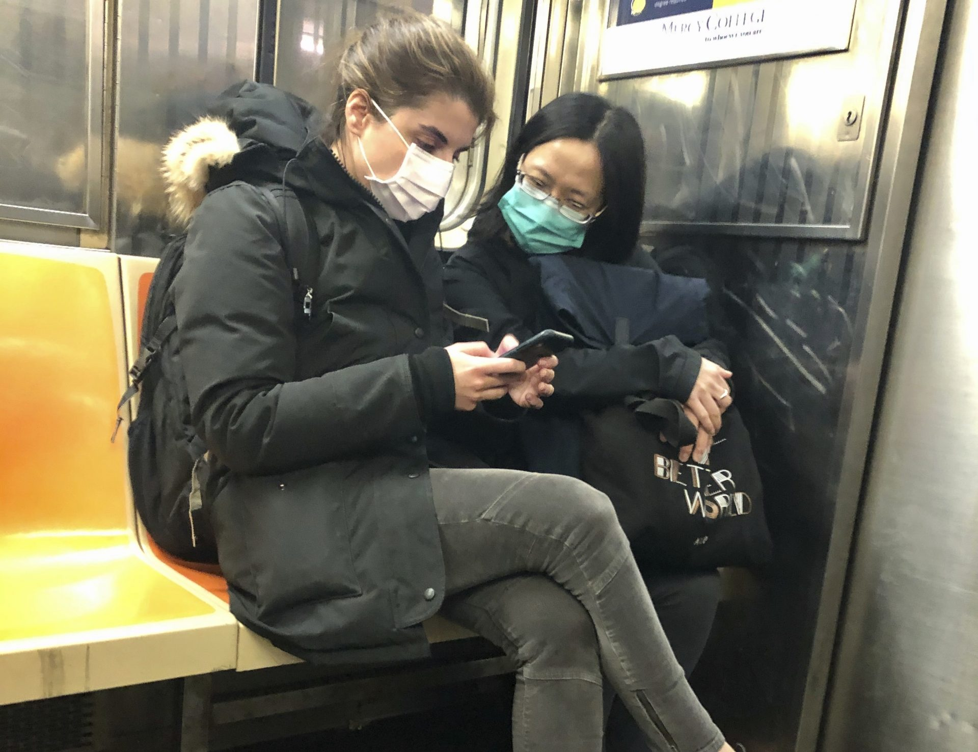 In this March 4, 2020 photo, two women wear masks as they ride a subway train, in New York. Two more cases of the new coronavirus have been confirmed in New York City, raising New York state's total to 13, Mayor Bill de Blasio said Thursday.